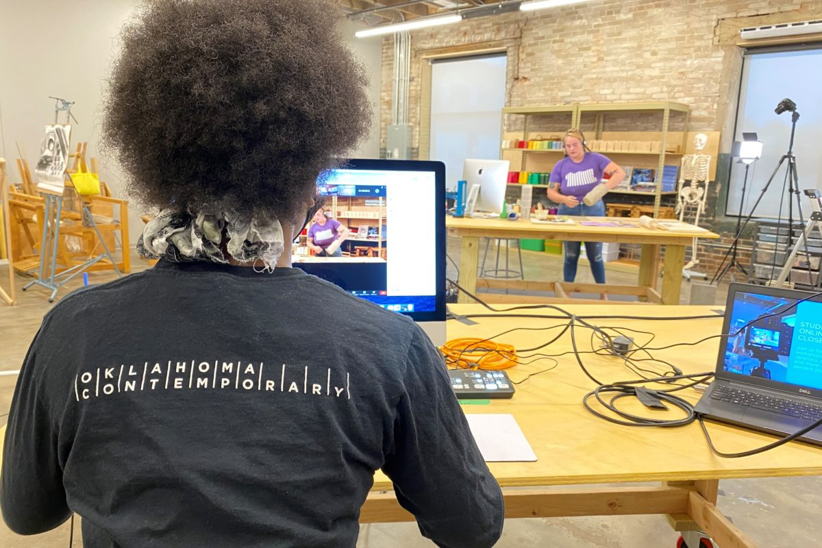 A person sits in front a computer recording an instructor that can also be seen in the background