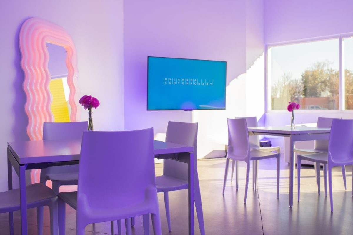 A room filled with white tables features a mirror with a lighted plastic frame, a TV screen and windows