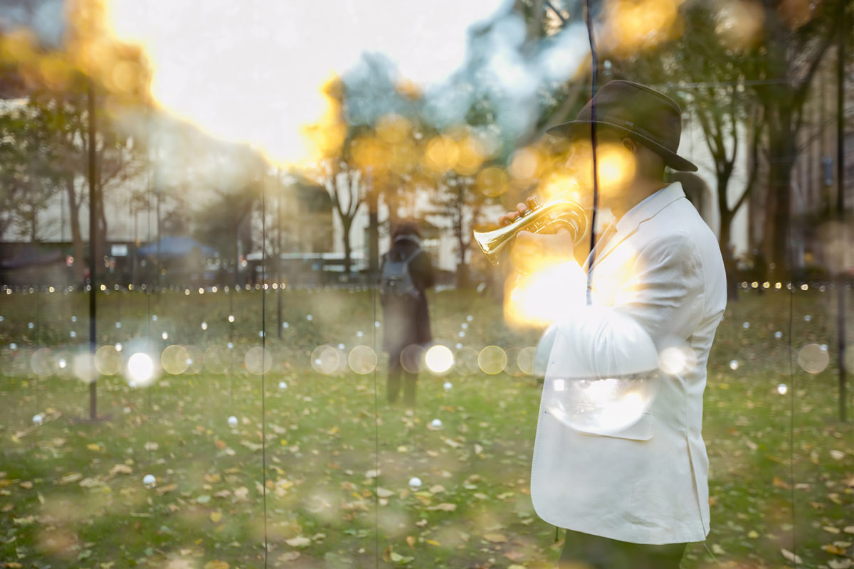 Camera flares blur in front of a person in a white jacket and black hat playing the trumpet on a grassy lawn