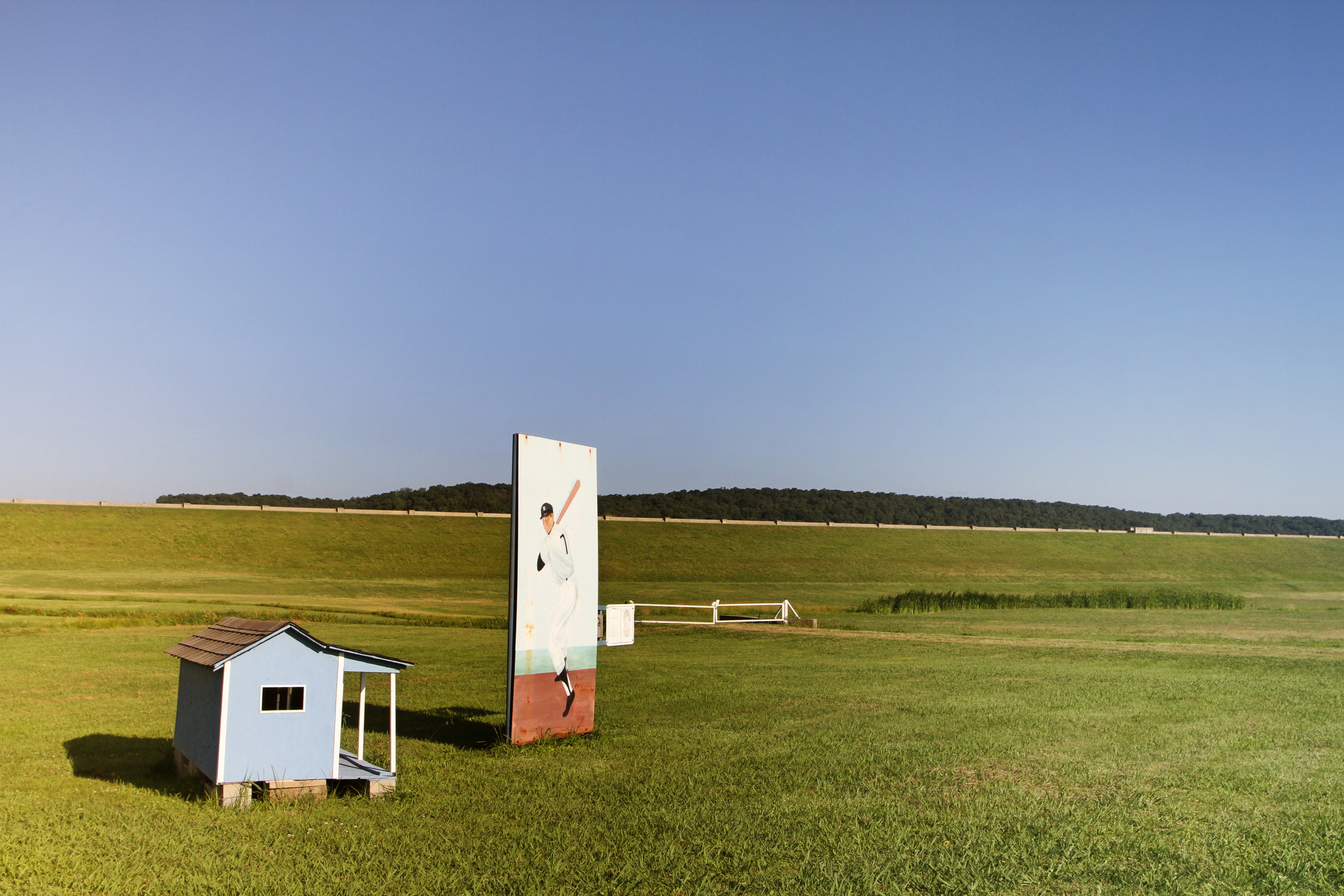 A photograph depicts a large artistic rendering of a baseball player next to a small shed on a prairie underneath a blue sky