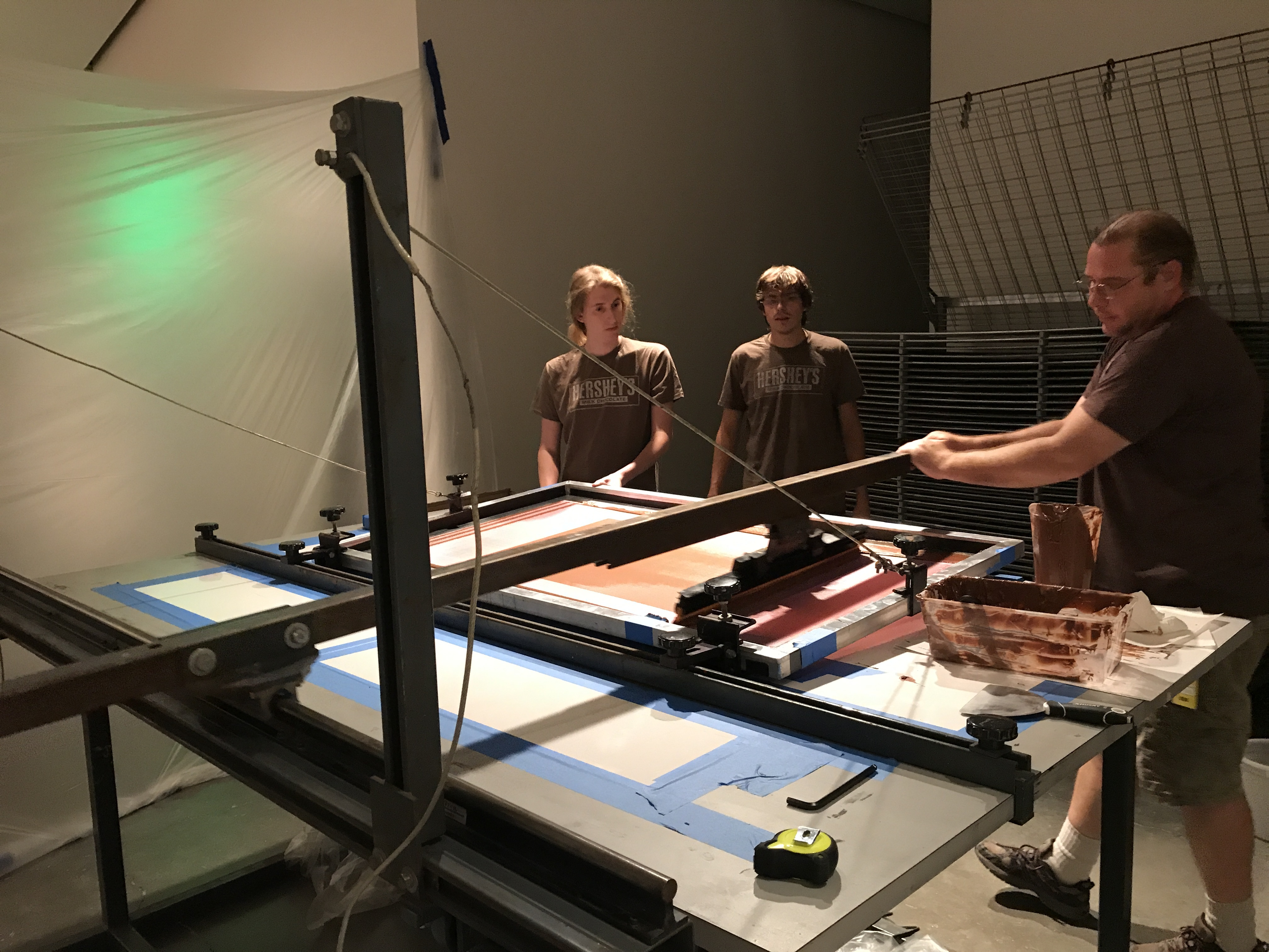 Three people operate a large screenprinting device