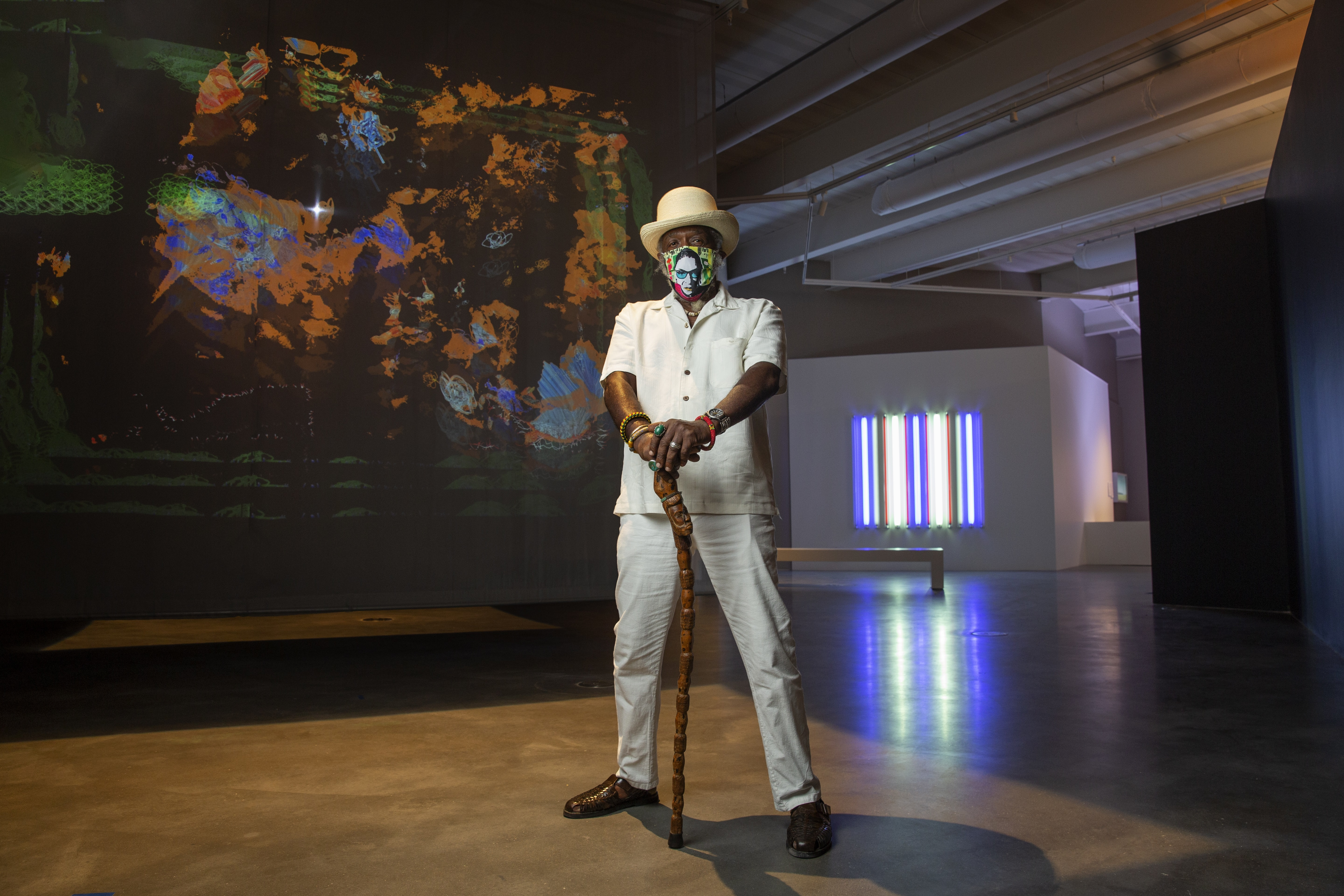 A masked figure poses in front of contemporary works of art in a gallery space