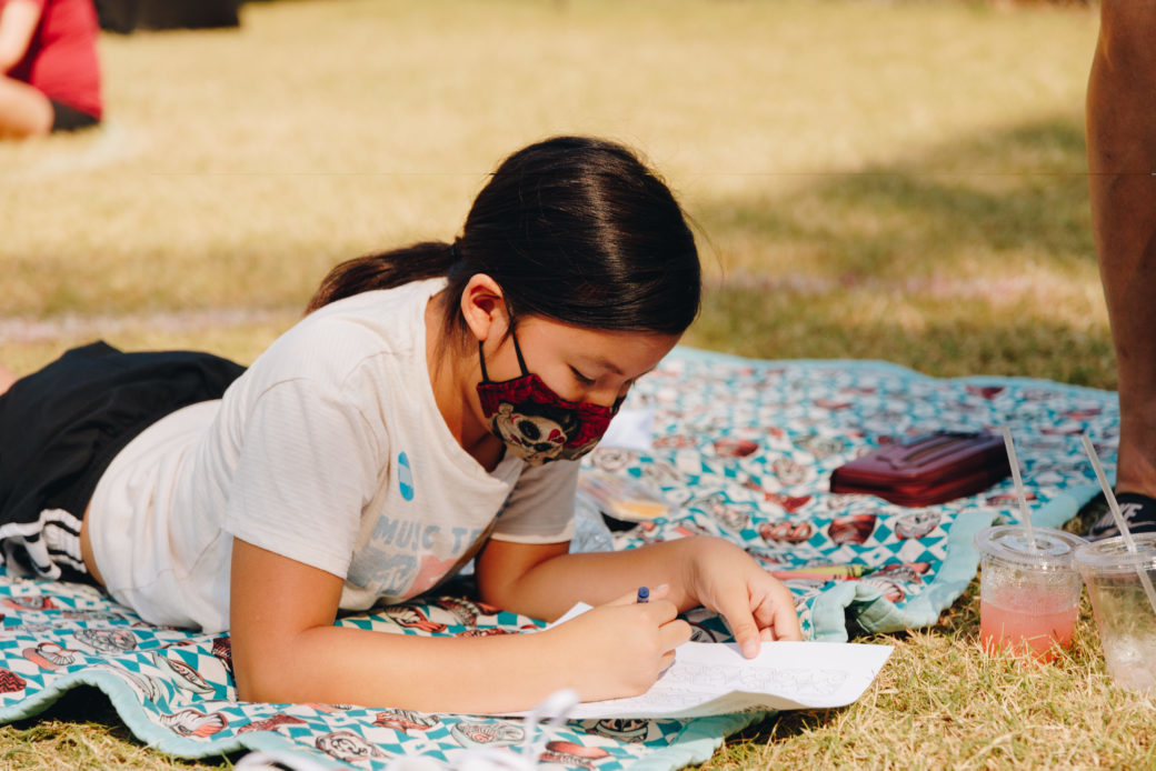 A child works on an art project on a blanket spread out on the grass in the daytime