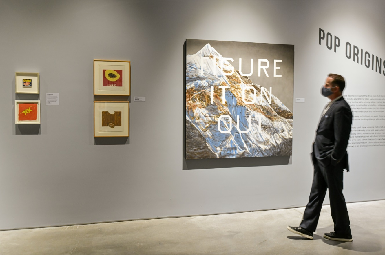 "A person stands looking at art on the wall, including a painting of a mountain overlaid with the words ""FIGURE IT ON OUT,"" in a gallery"