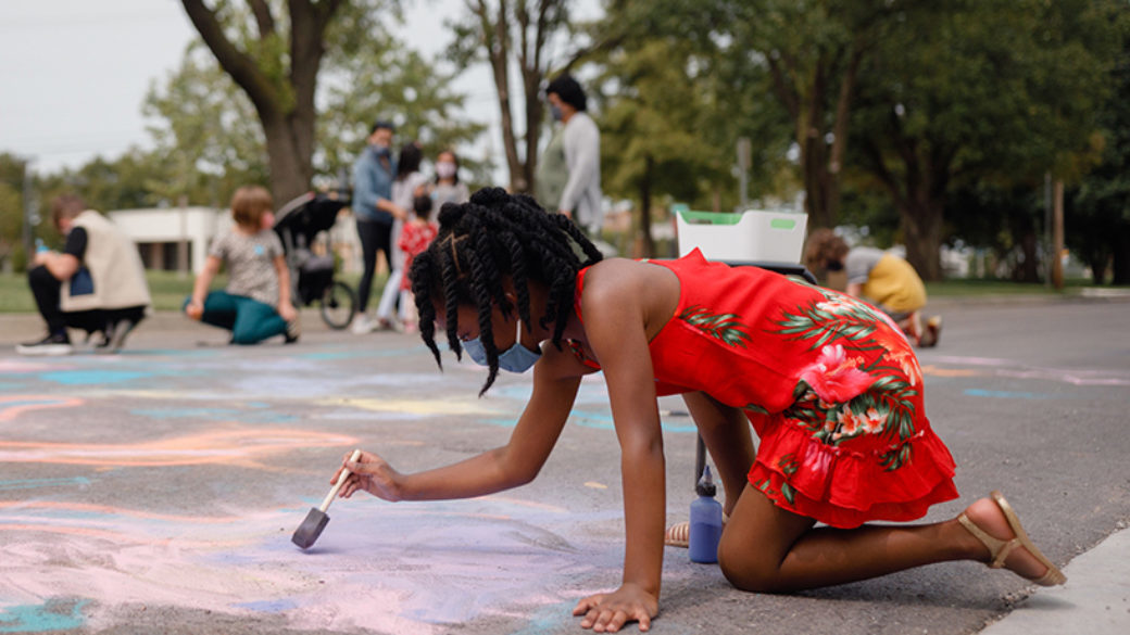 A child in a red dress paints on the concrete, on all fours