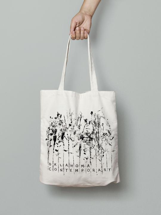 "A hand grips the handle of a tote bag screenprinted with flowers, depicting the words ""Oklahoma Contemporary"""