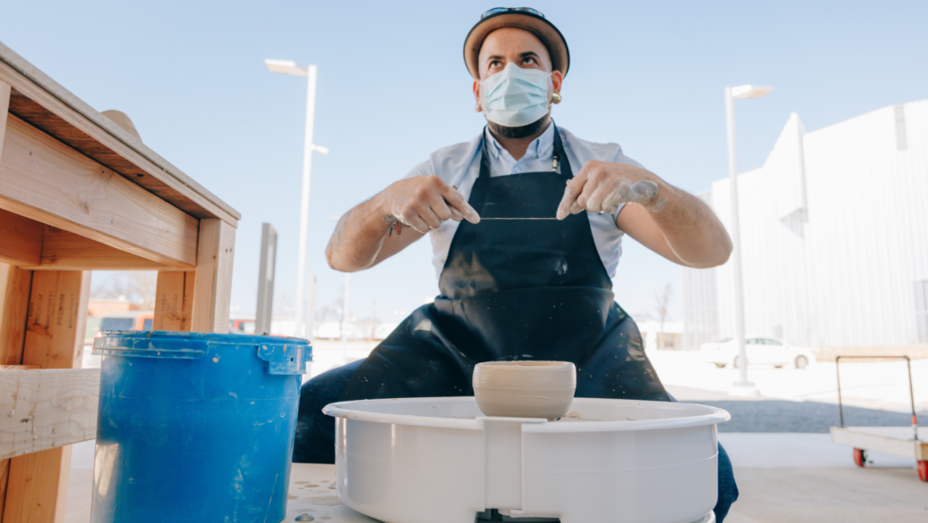 A person wearing a face mask, brimmed hat and apron sits at a ceramics wheel spinning clay