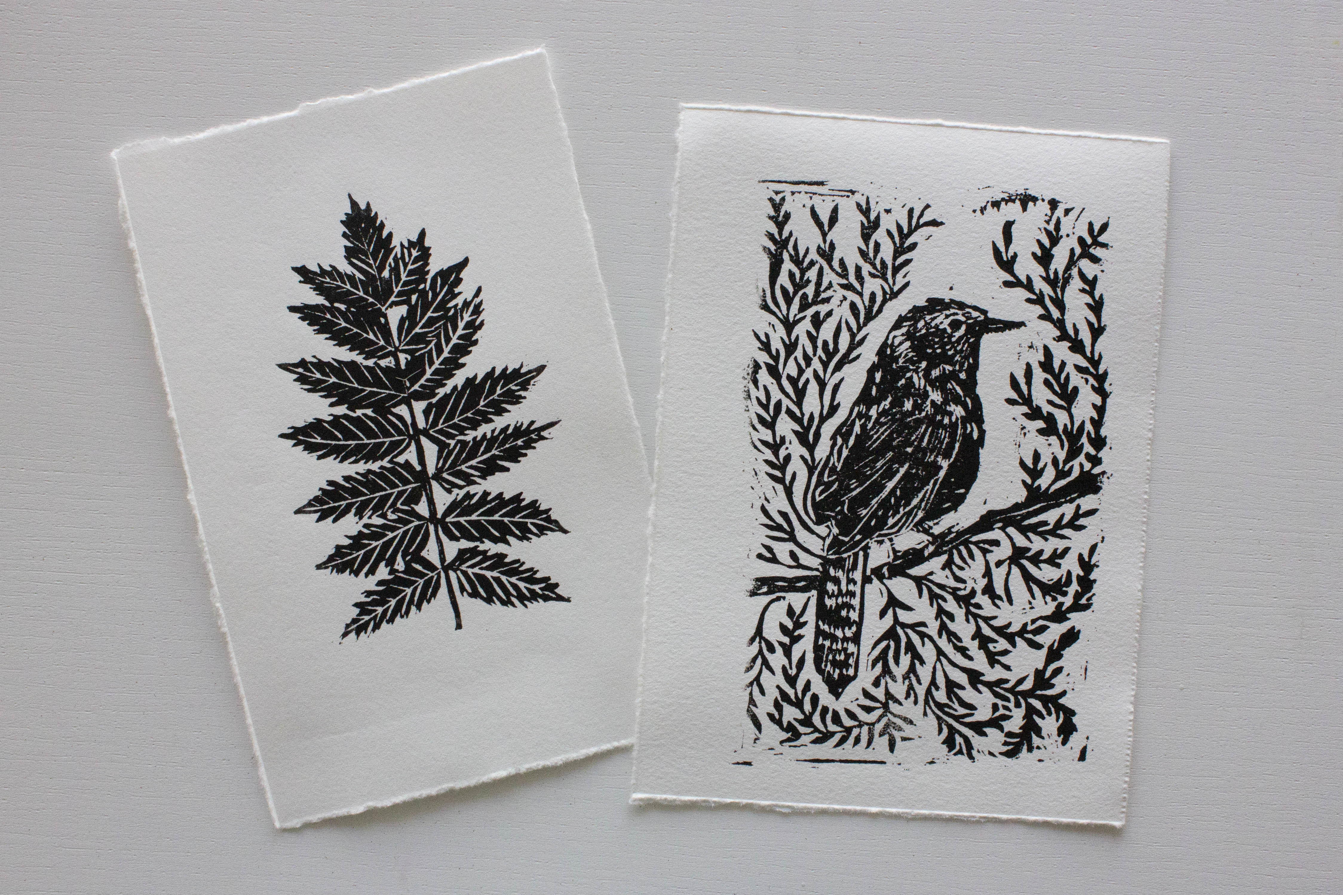 A photograph of two black-and-white art prints: a leaf on the left and a bird on a branch on the right