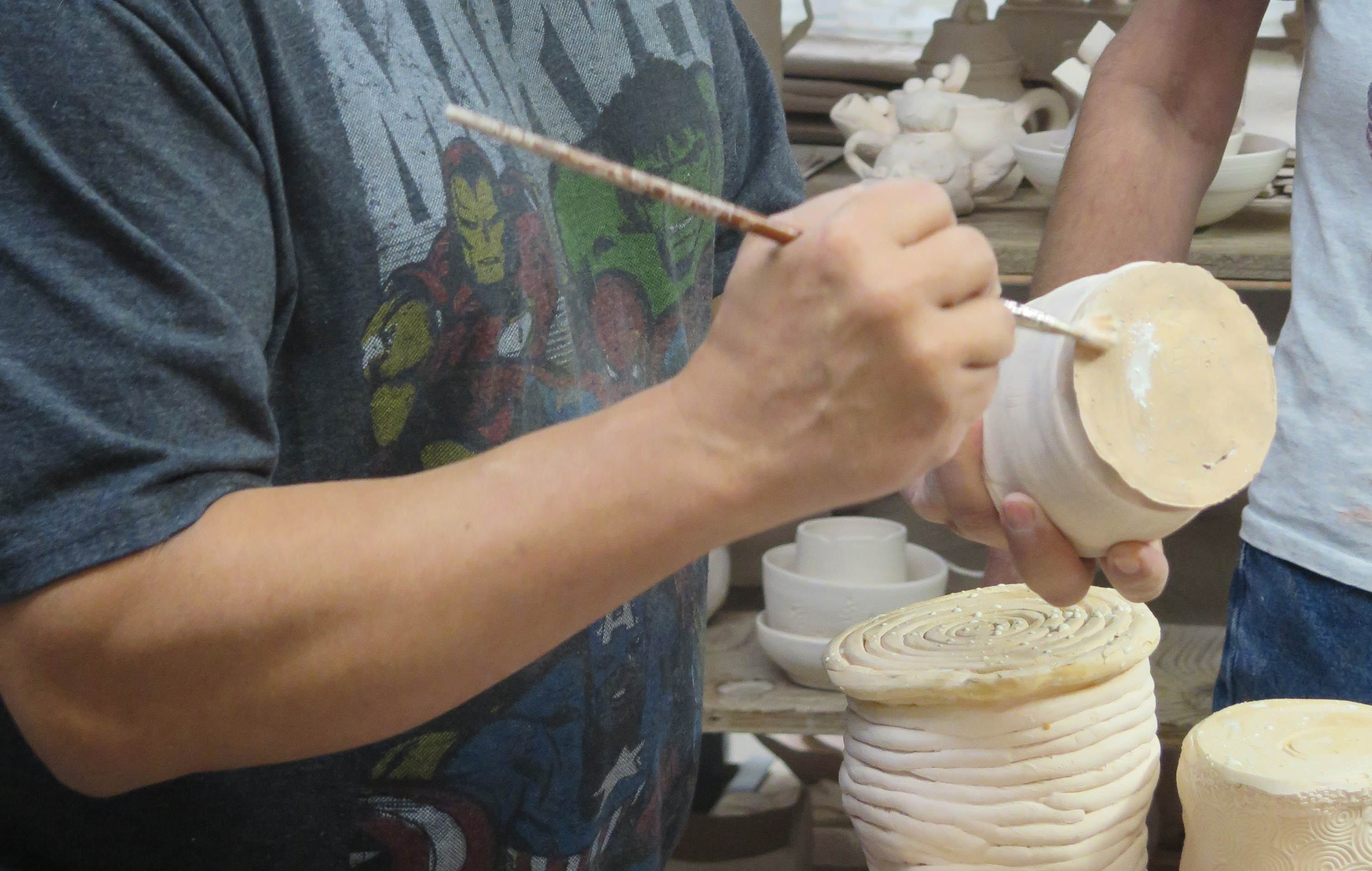 A cropped photo of hands painting a ceramic vessel