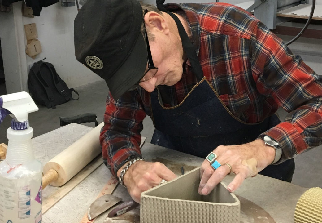 A figure in a ball cap and plaid shirt works on a triangular ceramic piece