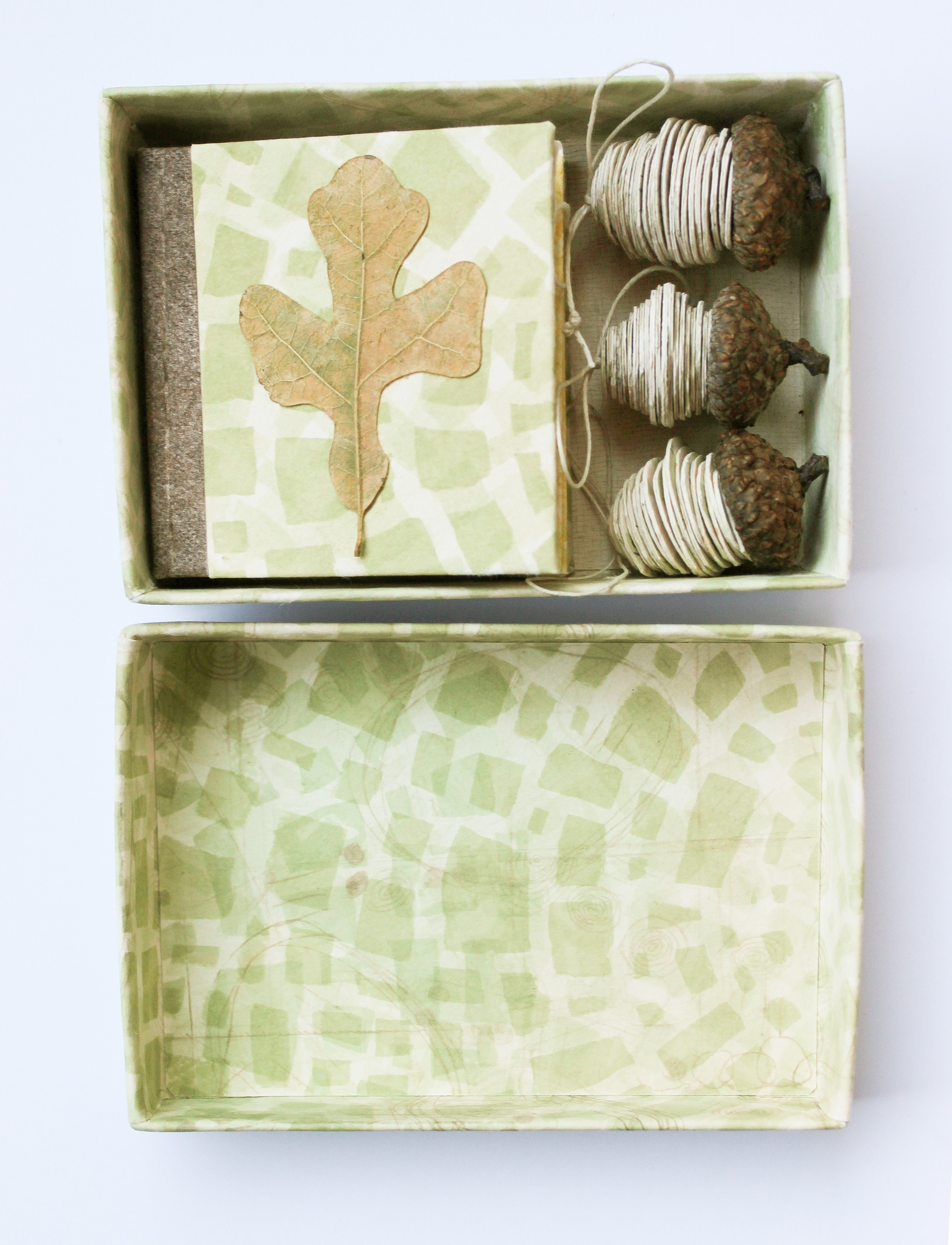 A photo of a patterned box holding string-wrapped acorns and a handmade book with a leaf on the front