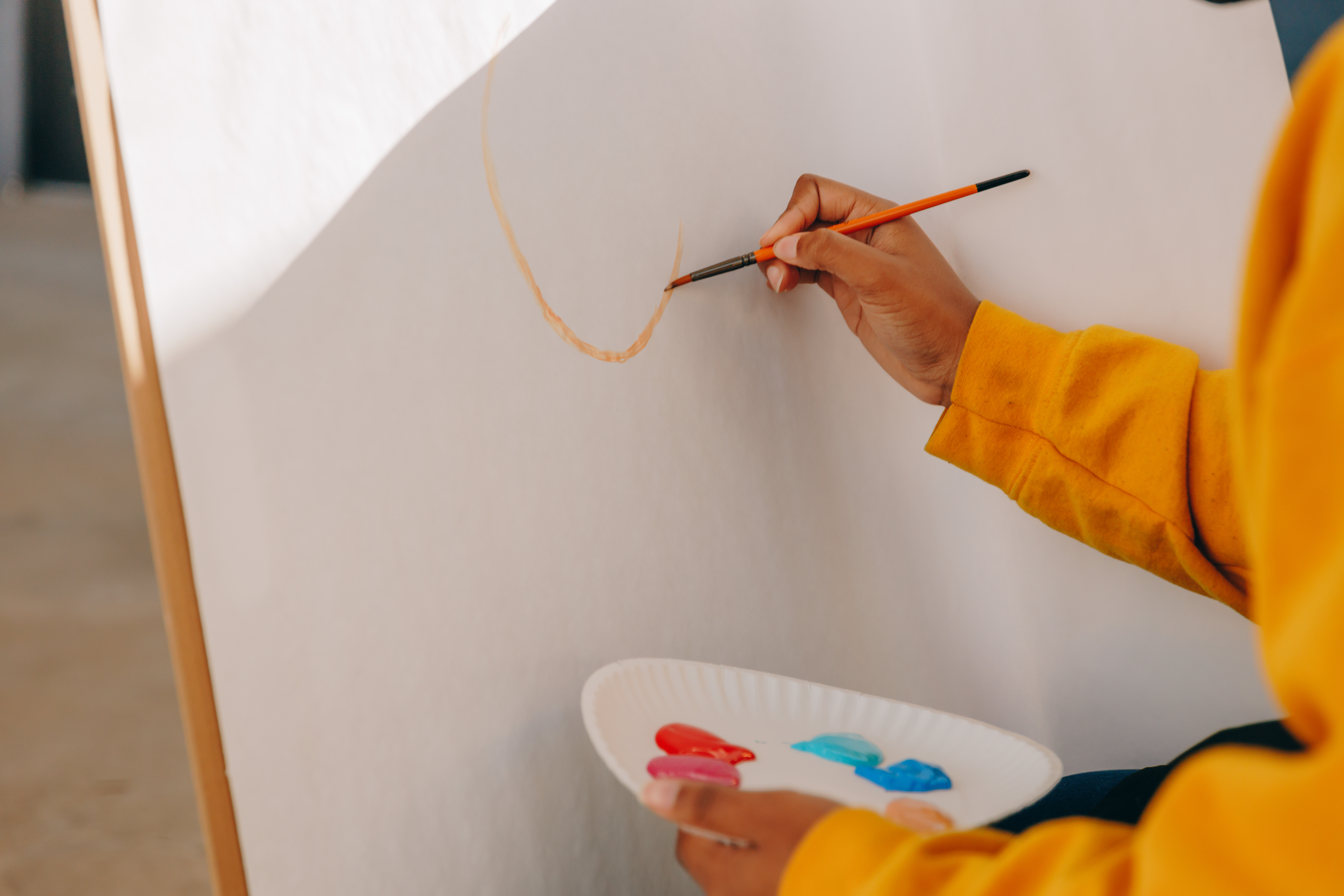 A tightly cropped photo of dark-skinned hands working on an easel outdoors