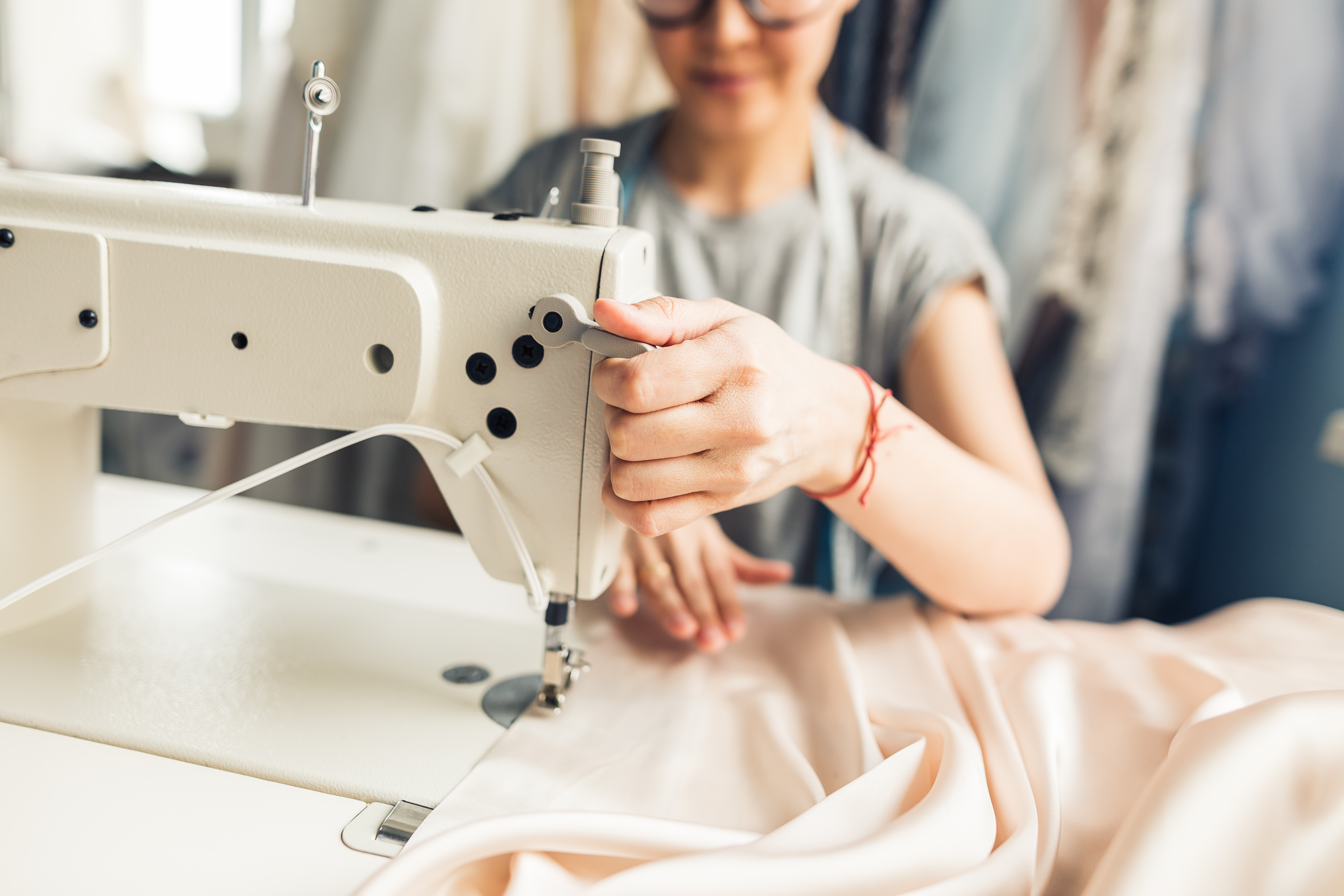 An out-of-focus figure works at an in-focus sewing machine
