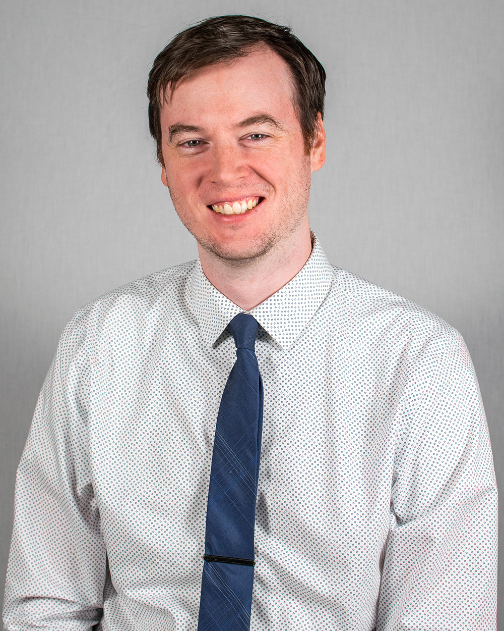 Smiling person with dark hair poses in a polka-dot shirt and blue tie