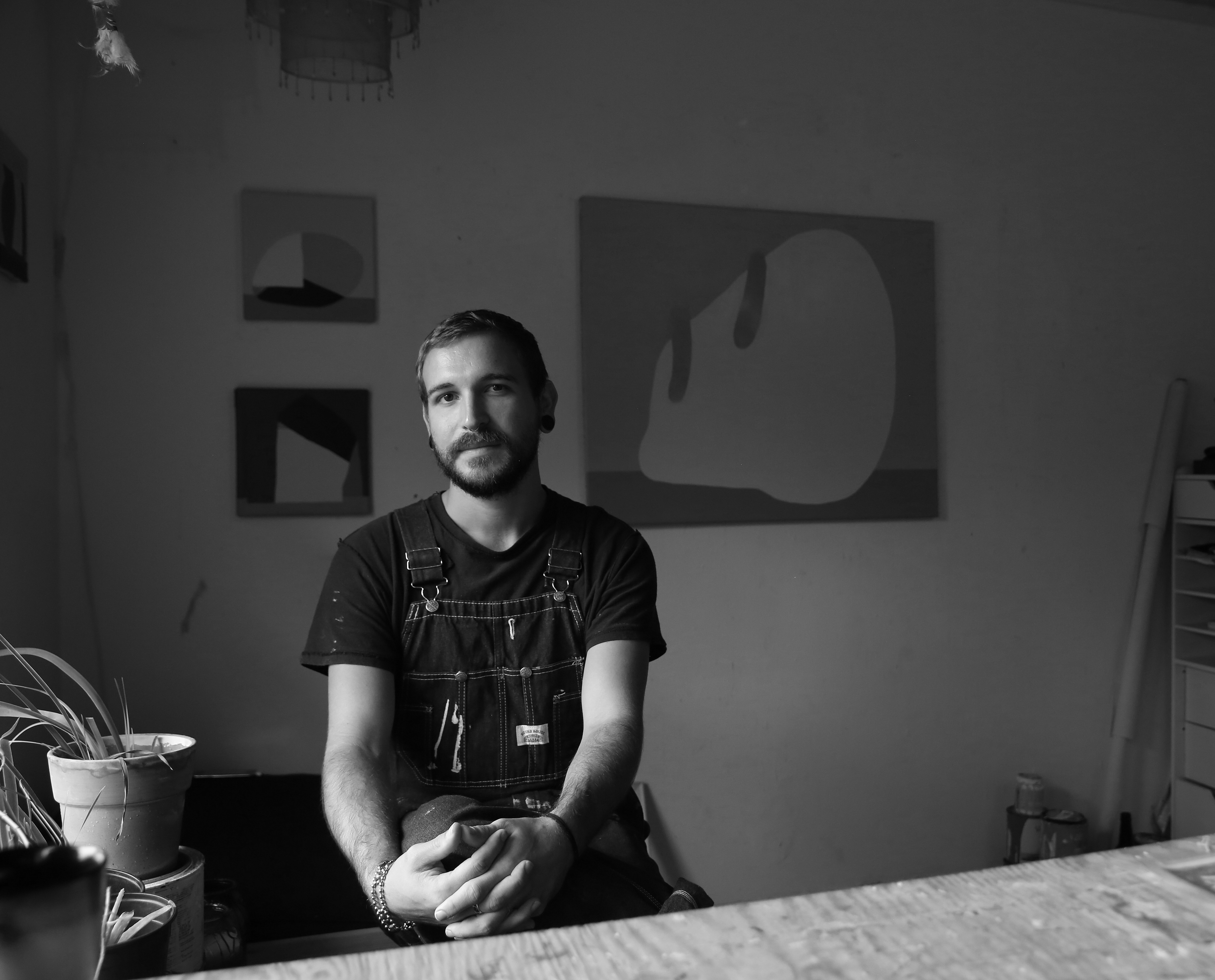 A person wearing overalls sits in a studio with abstract art on the walls