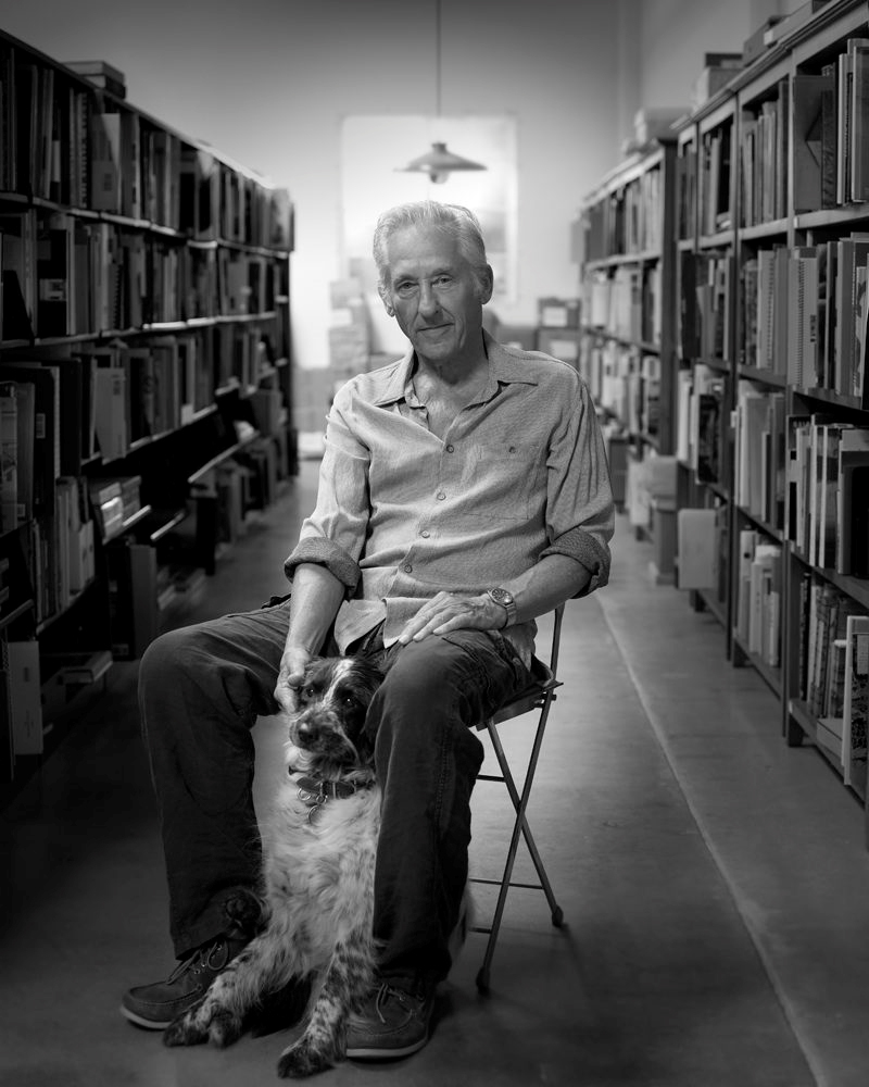 A black-and-white photo of an older man sitting between bookshelves with a dog at his feet