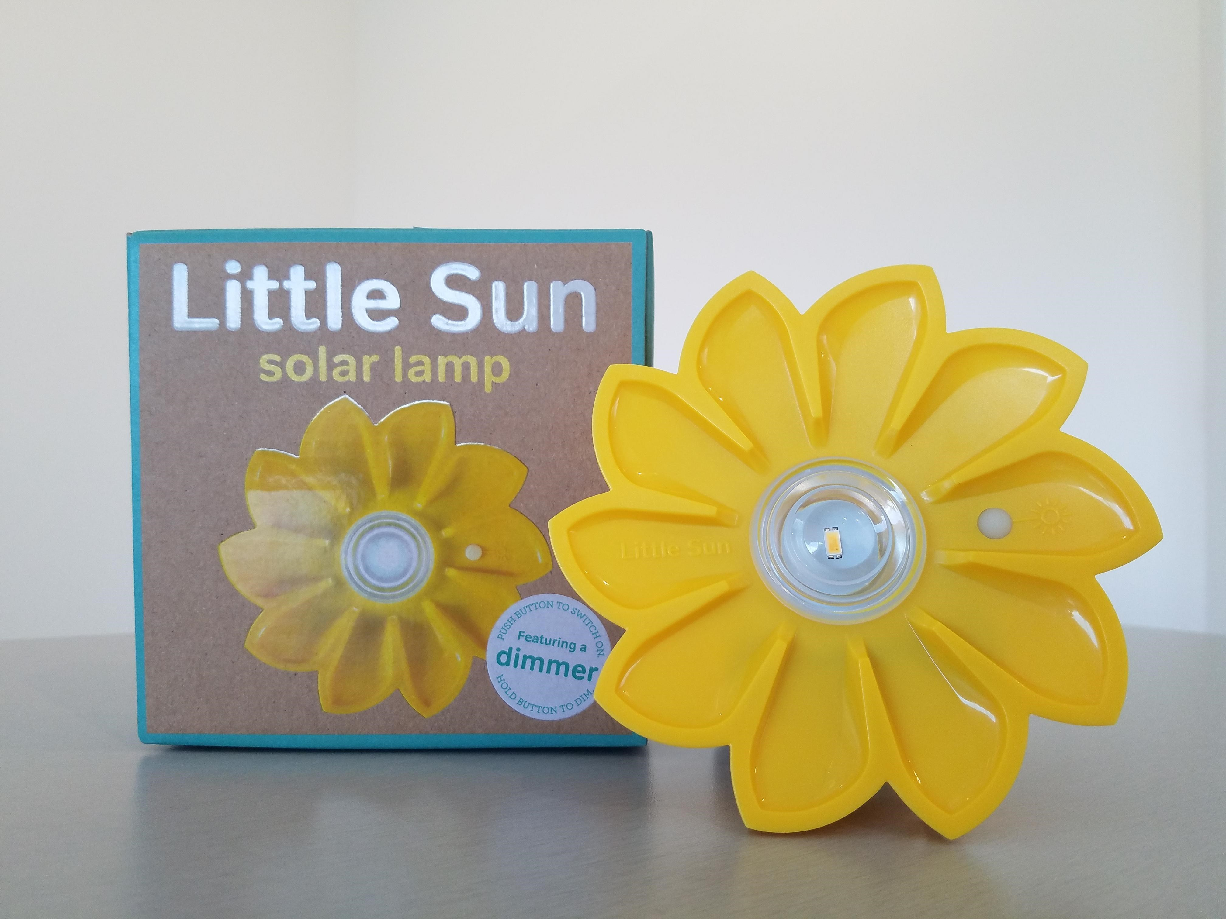 A plastic solar lamp is shaped like a yellow flower