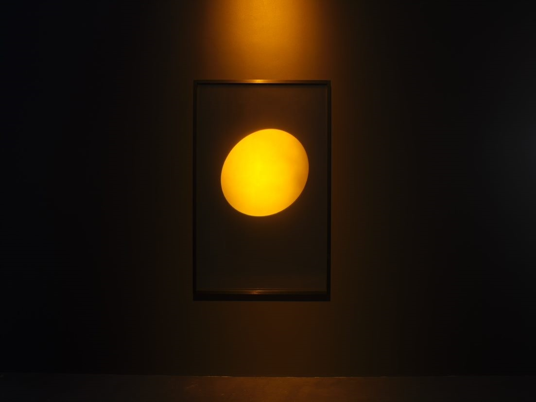 A photo of a glowing, spherical orange hologram hung on a wall