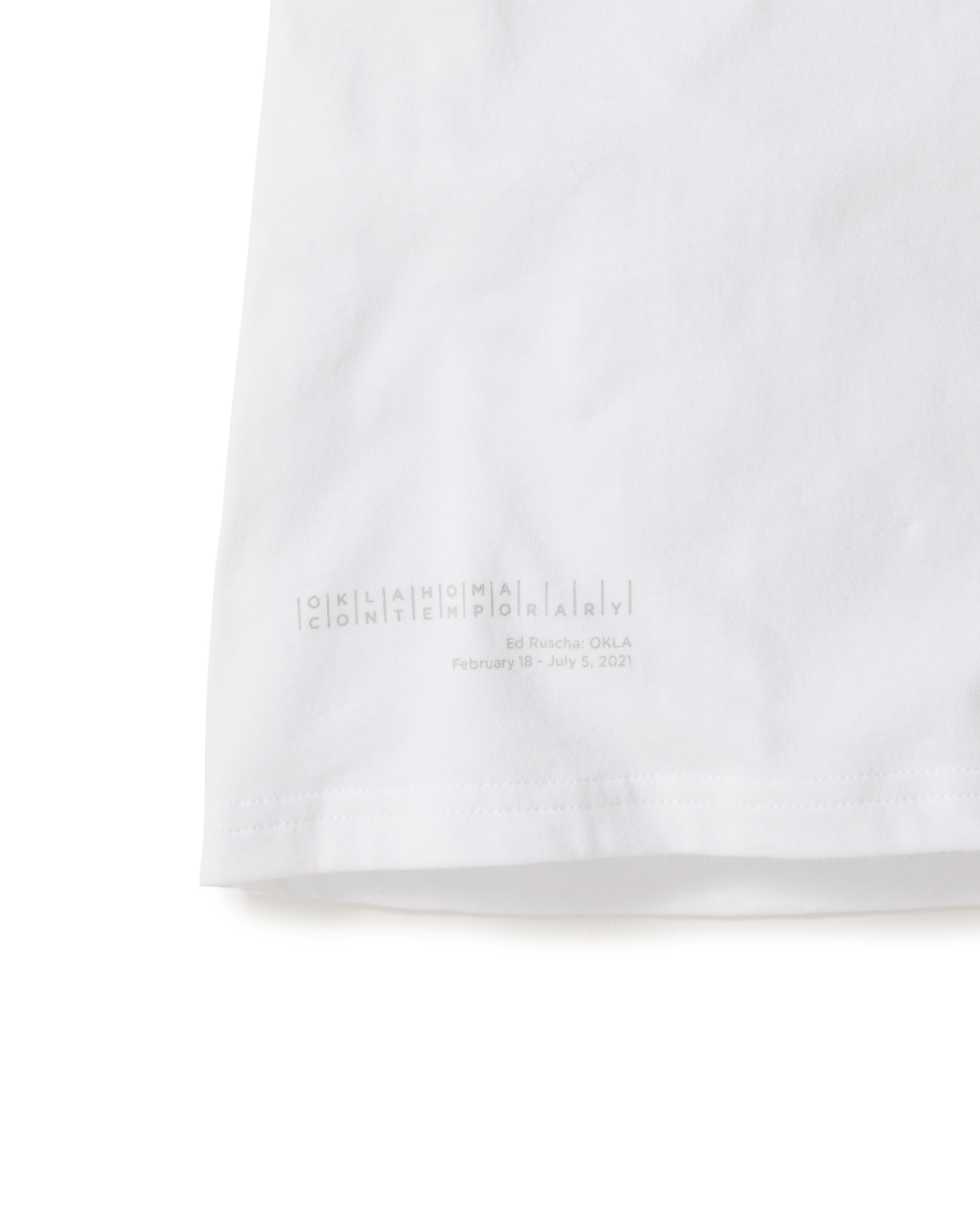 Cropped photo focusing on the lower left quadrant of a white T-shirt, depicting a logo featuring the words Oklahoma Contemporary