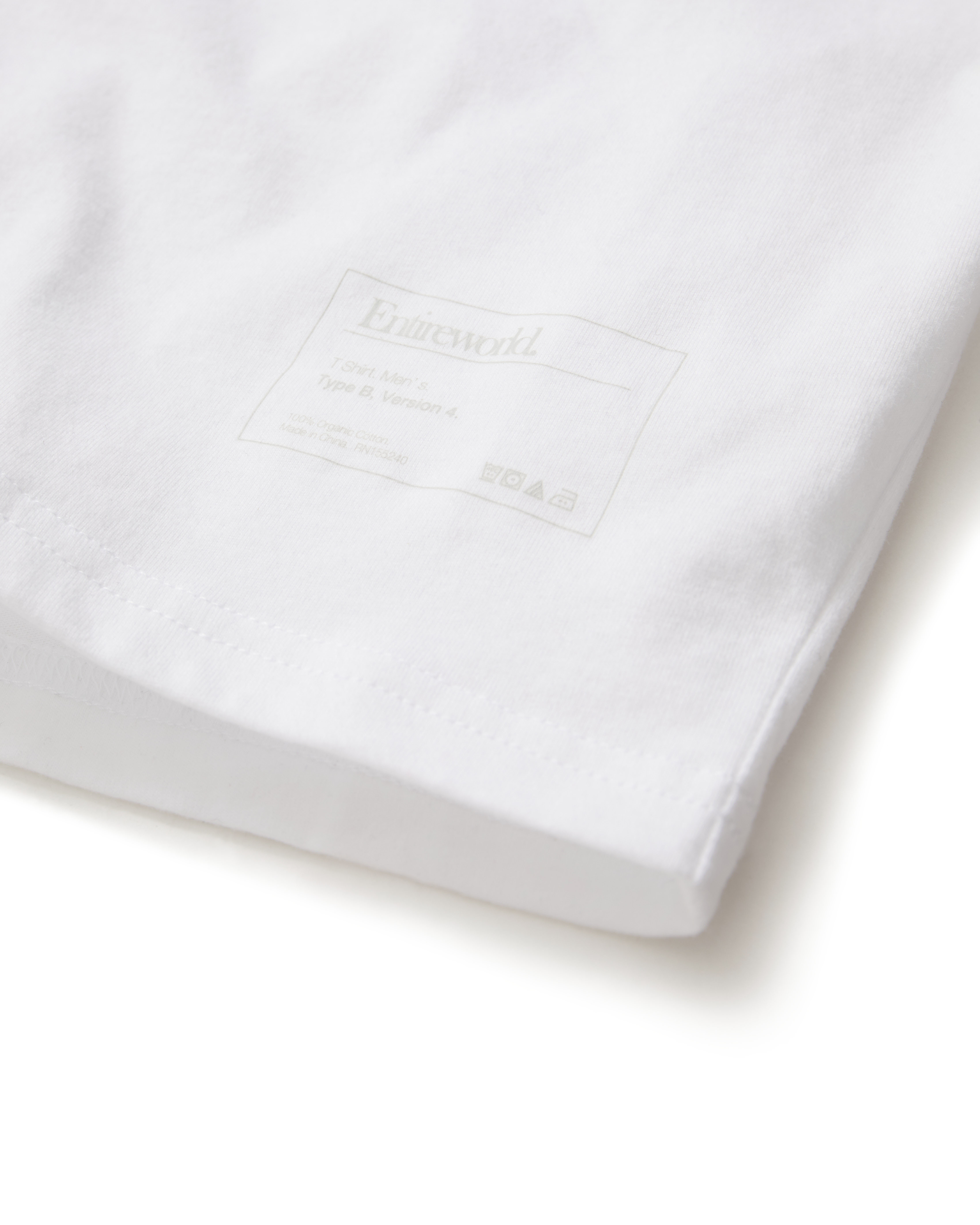 Cropped photo focusing on the lower right quadrant of a white T-shirt depicting the word Entireworld