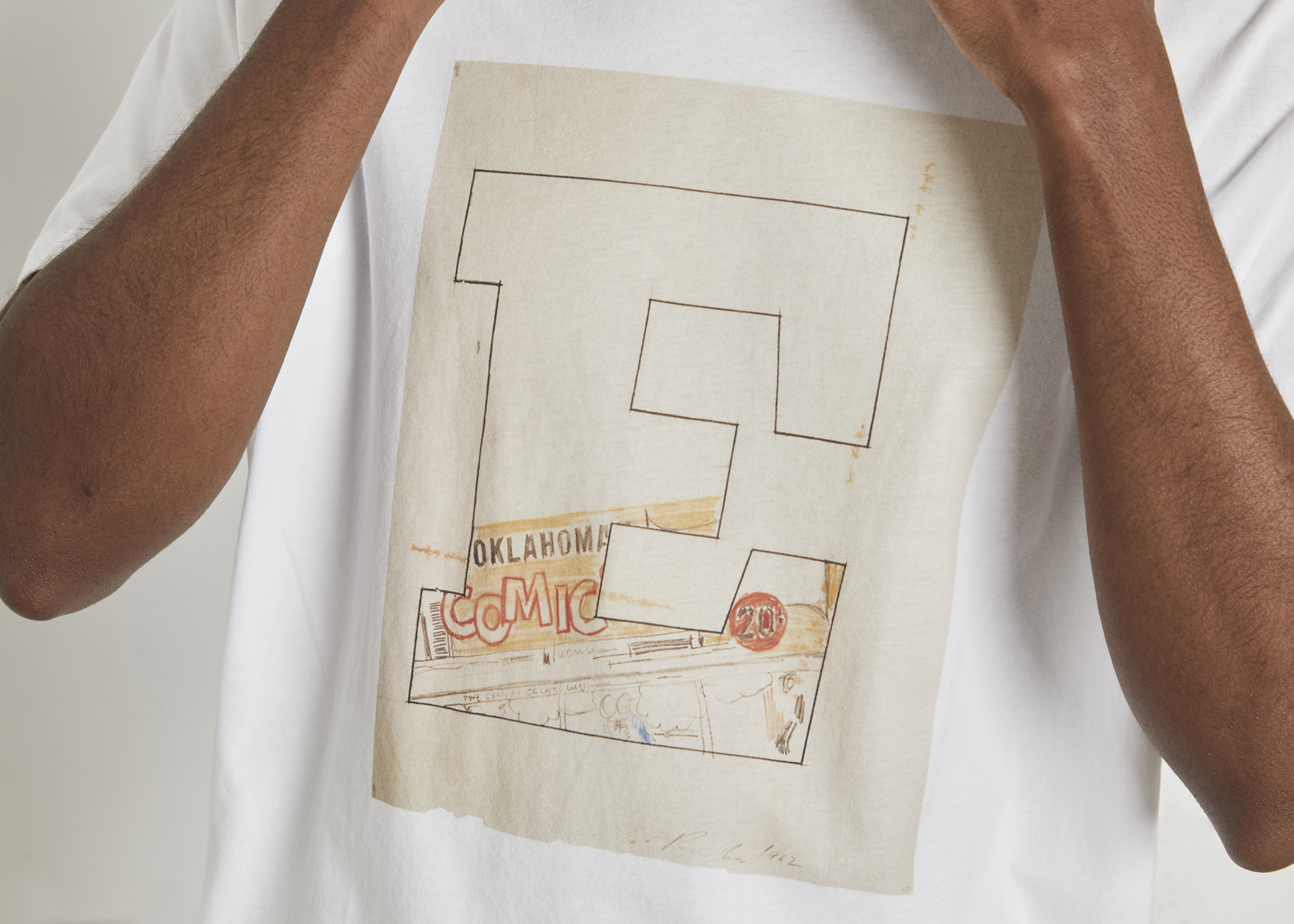 Cropped photo depicts a person wearing a white T-shirt emblazoned with a large letter E