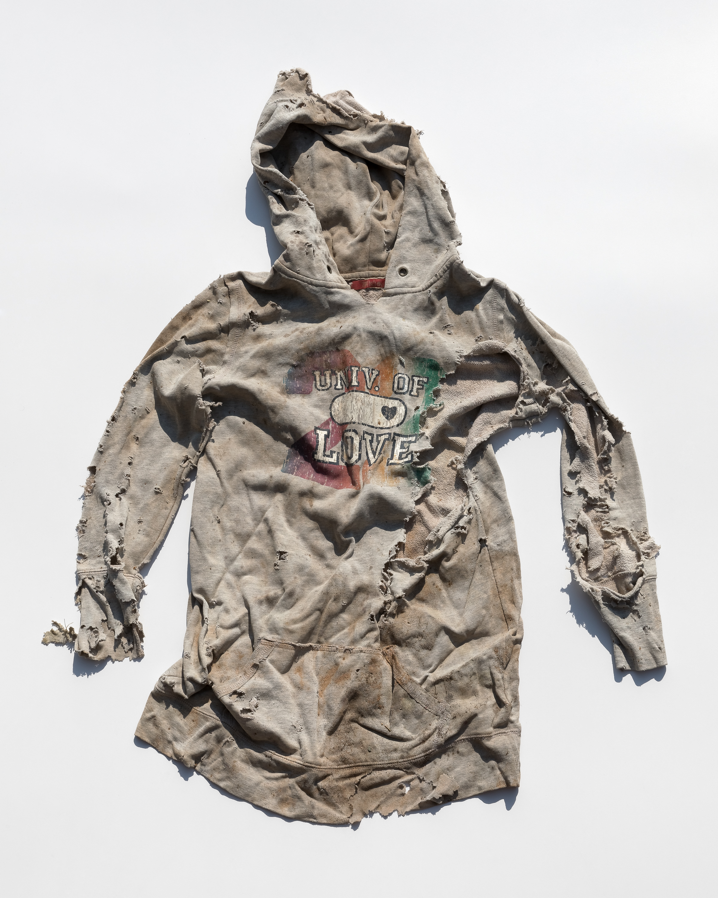 A severely rumpled, torn and dirty gray hooded sweatshirt depicts the text: Univ. of Love