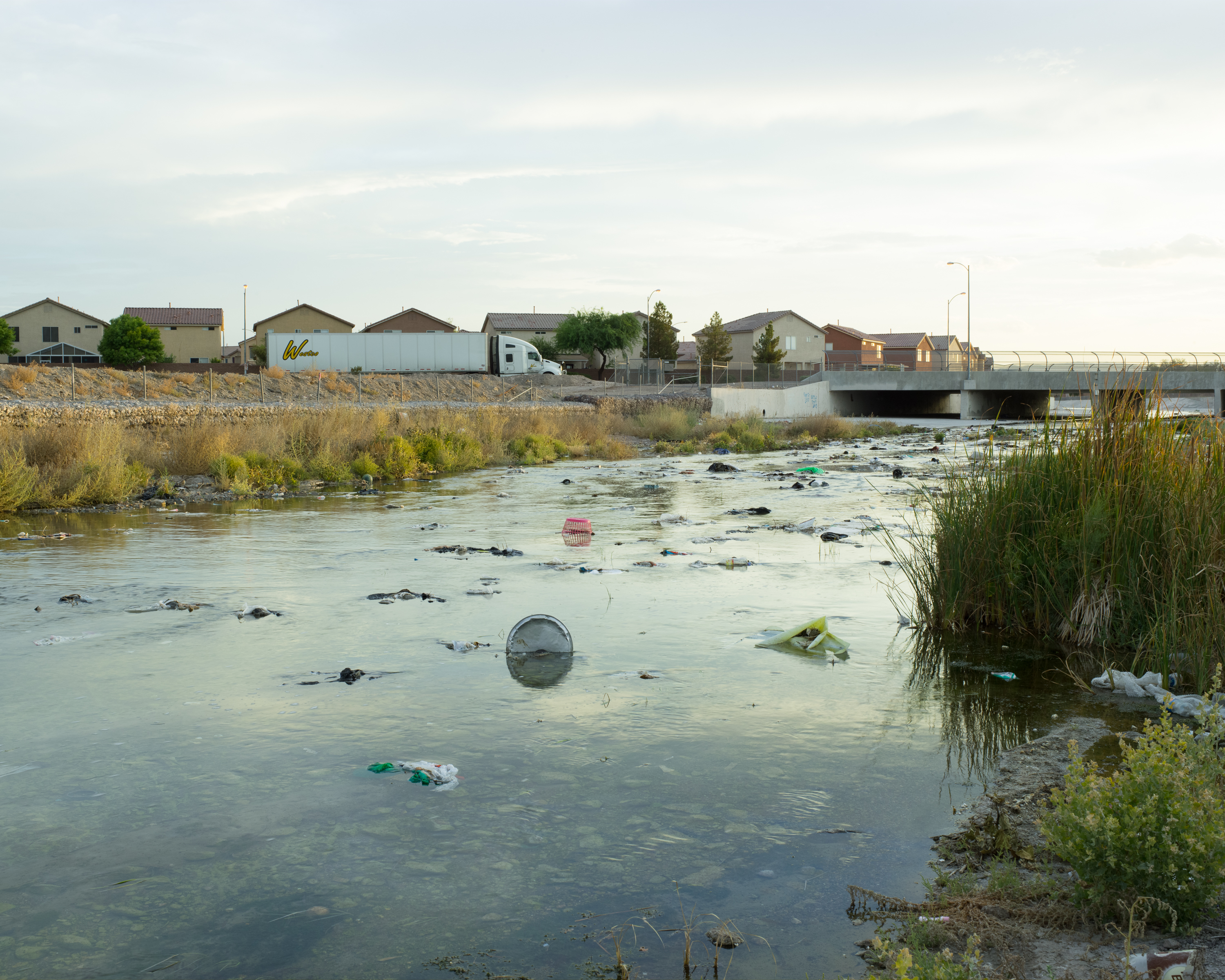 A river polluted with trash and everyday household items gives way to dense housing development and a semi-truck crossing a bridge in the background