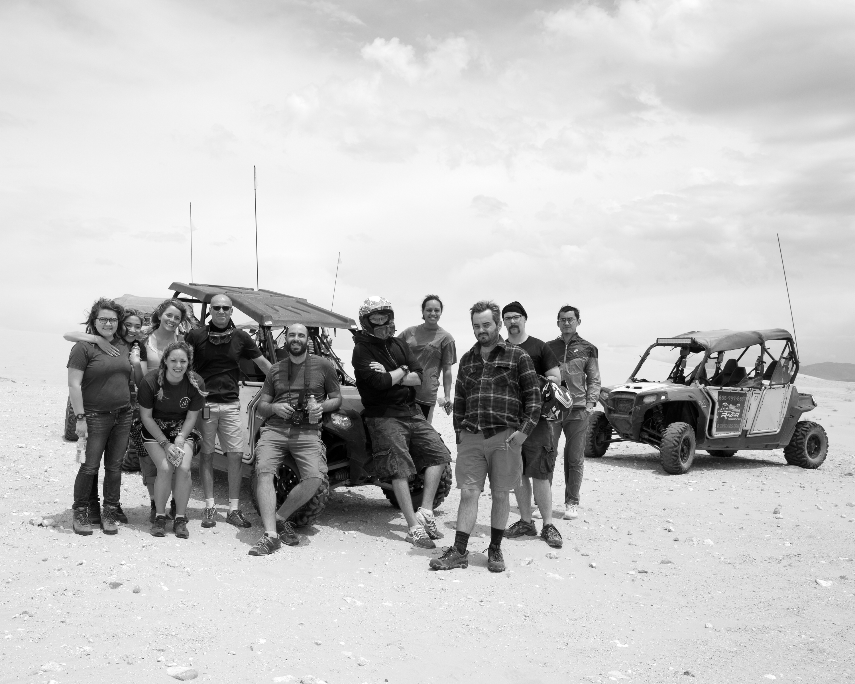 A black-and-white photo featuring a group of people leaning on a dune buggy in a sandy desert