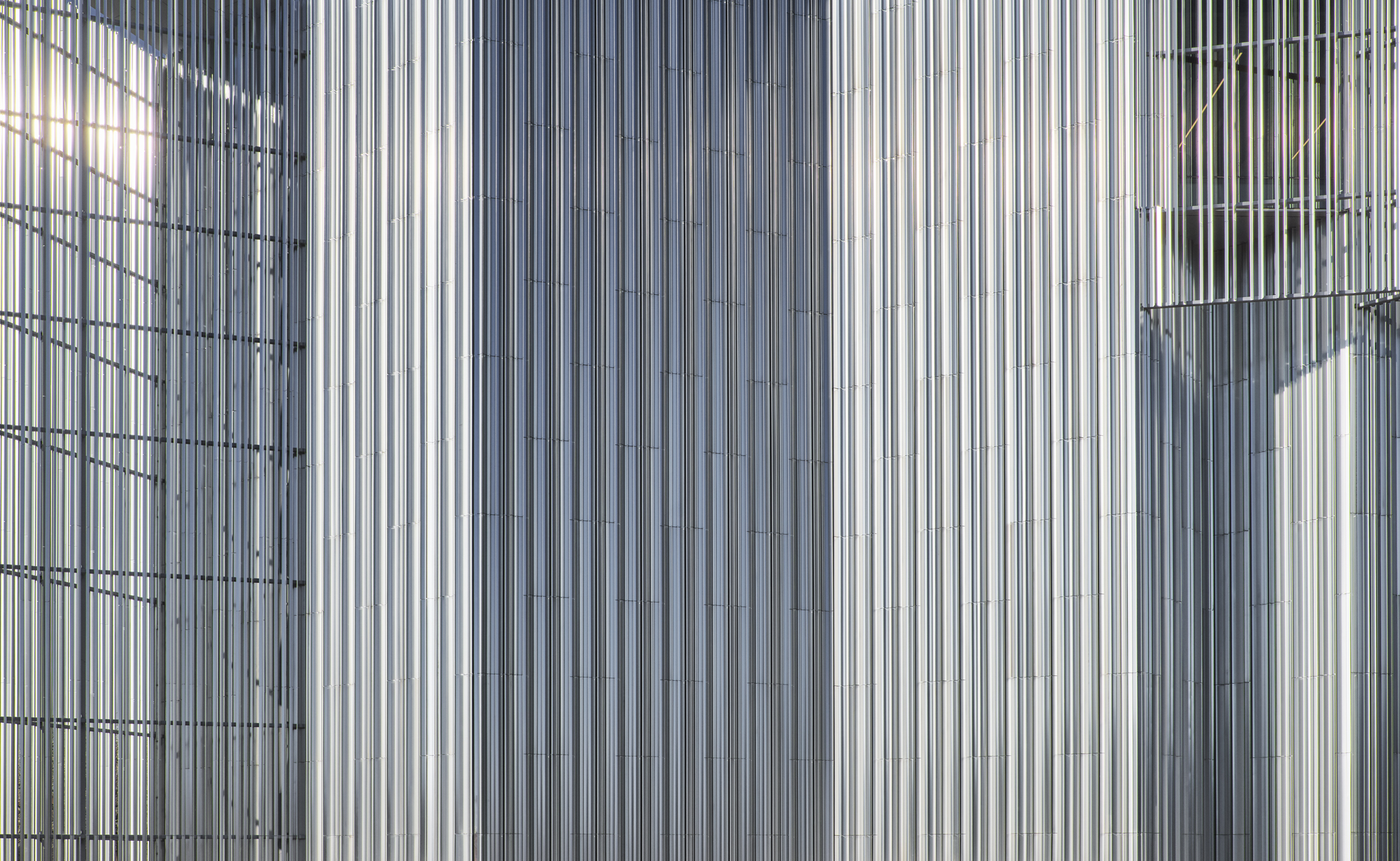 Tightly cropped detail photograph of the metal exterior of a contemporary building
