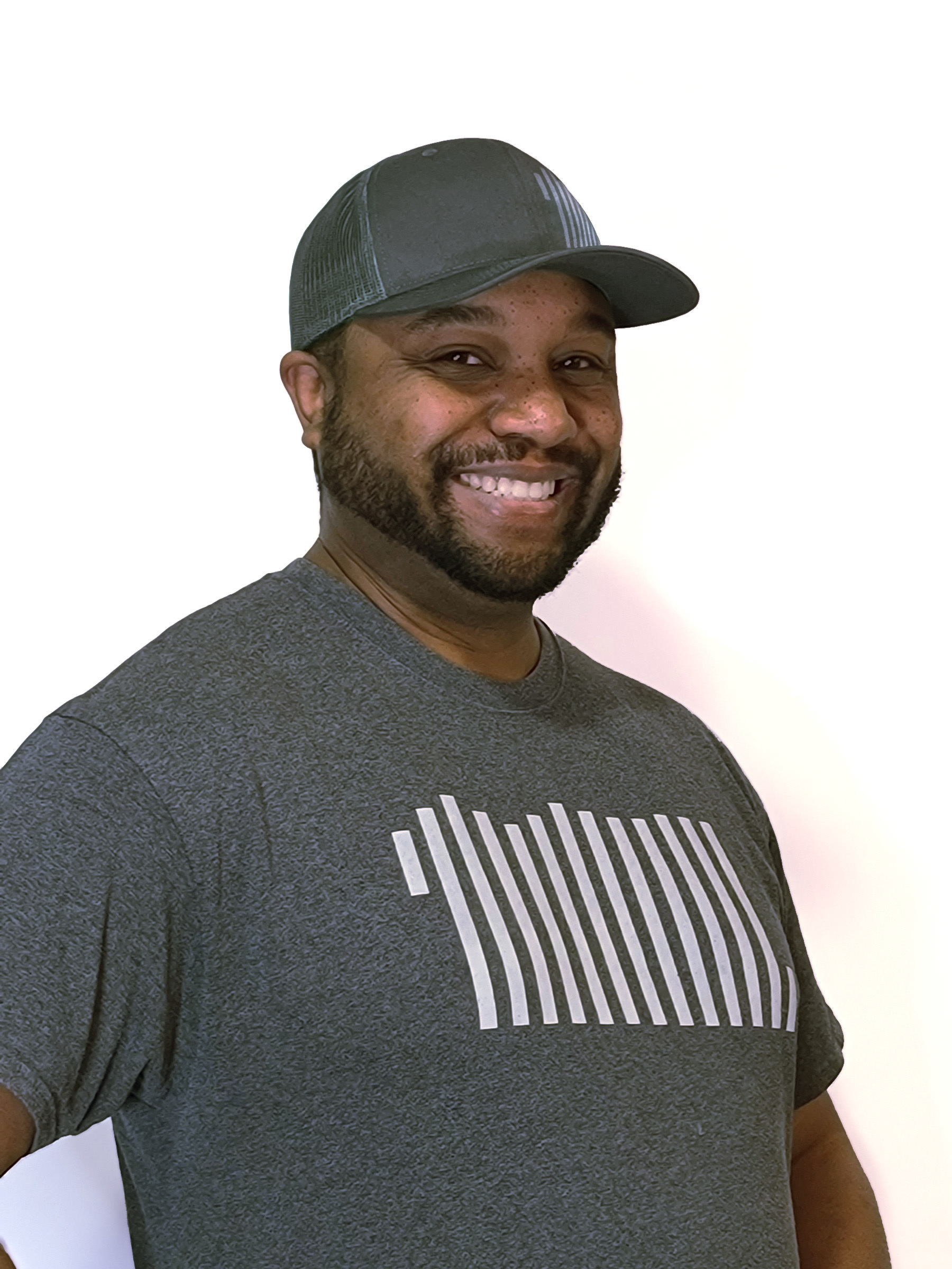 A person with a gray baseball cap and graphic T-shirt smiles at the camera