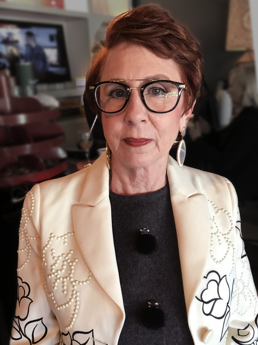A person with short red hair and thick glasses, wearing a white embroidered blazer over a black sweater, looks into the camera
