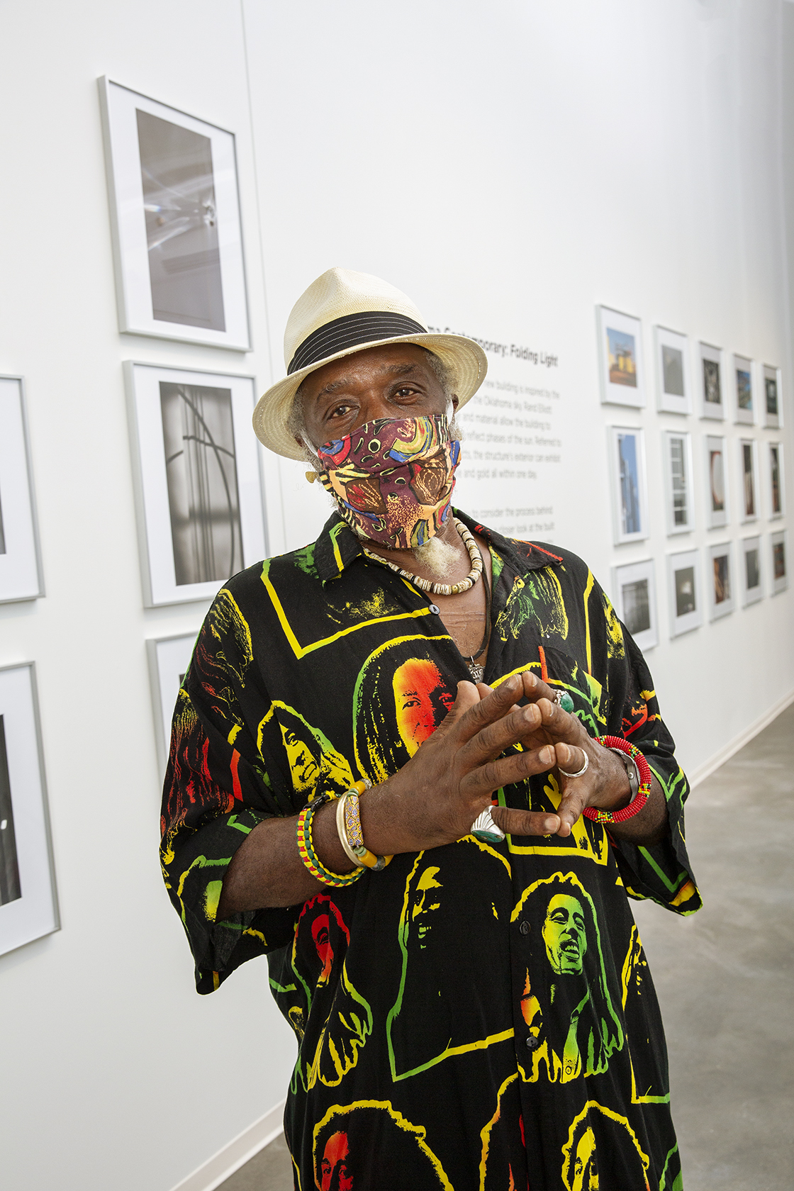 A man wearing a face mask and a black shirt with brightly colored lines stands in white gallery with numerous frames works