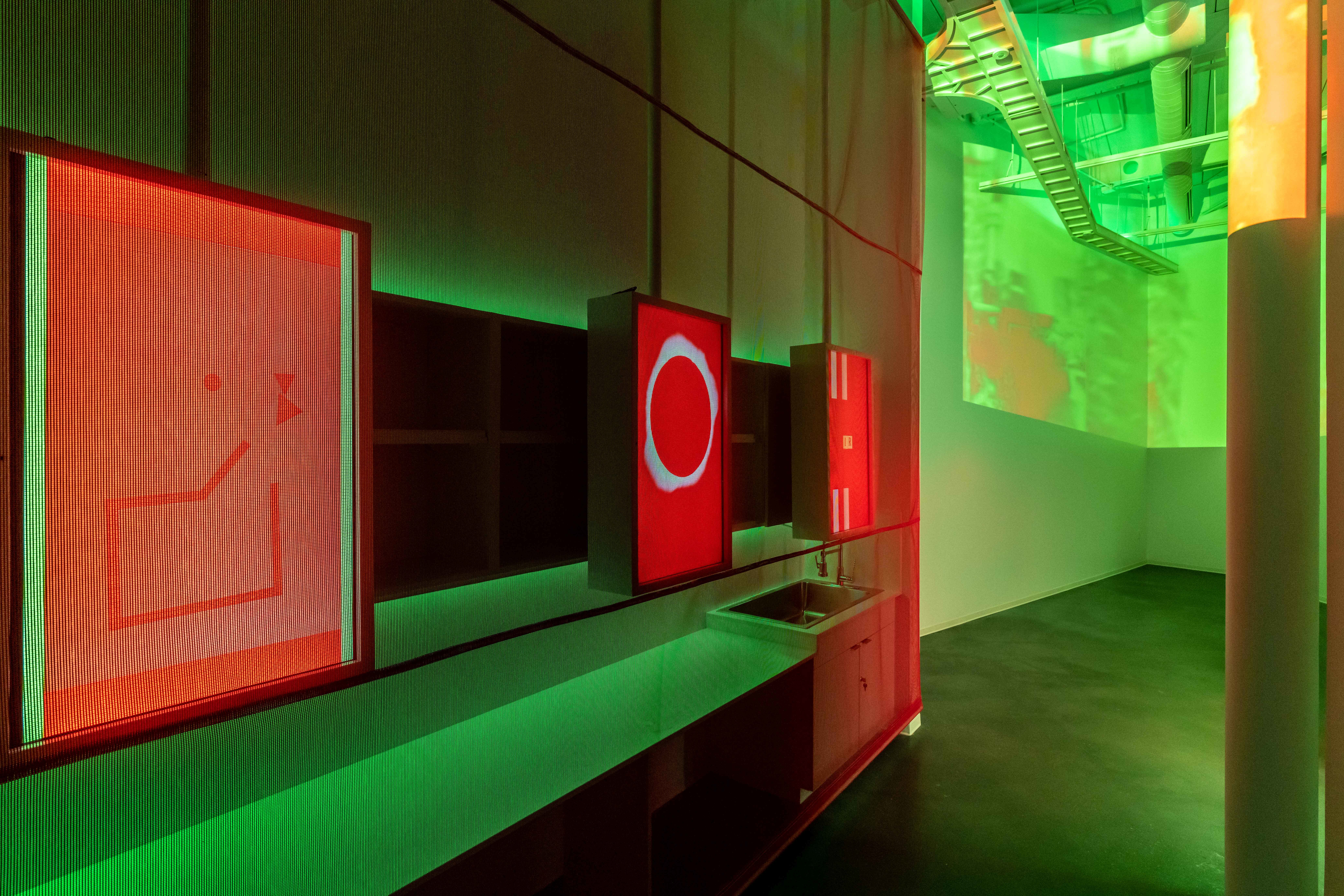 A small room shines with green light and red images on screens