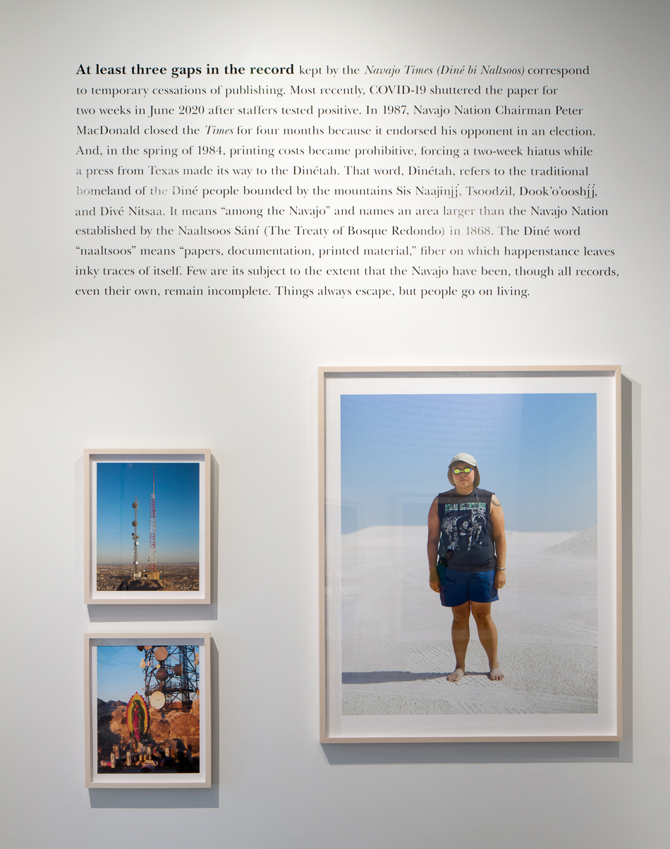 A white gallery wall features three framed photos (one of a person standing in the sand and two of industrial equipment) and a large block of text