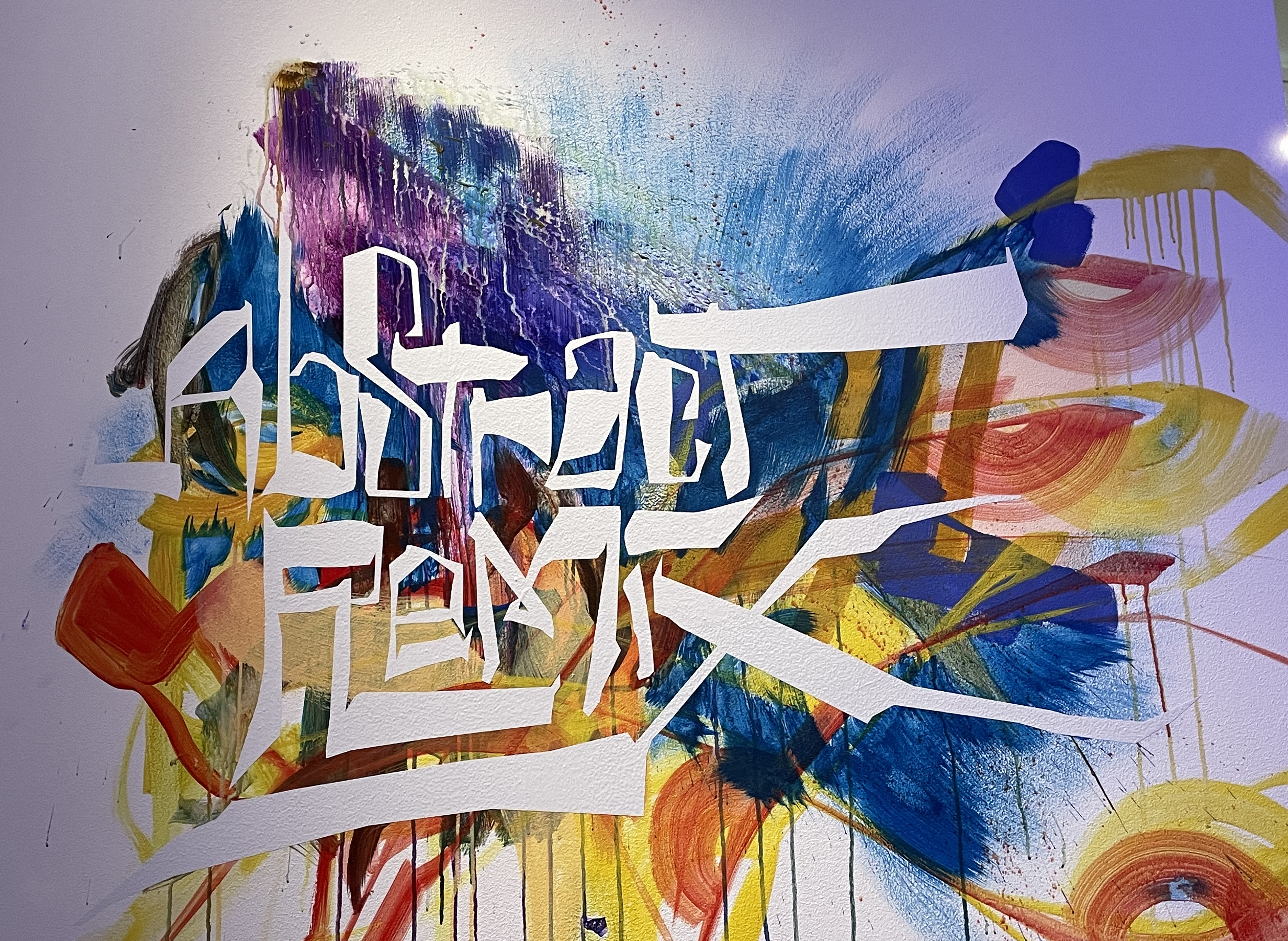 """The words """"abstract remix"""" appear in a white upon a wall smeared and splattered with colorful paint"""