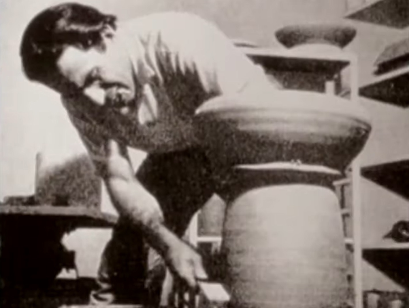 Black and white archive image of a person shaping a ceramic object
