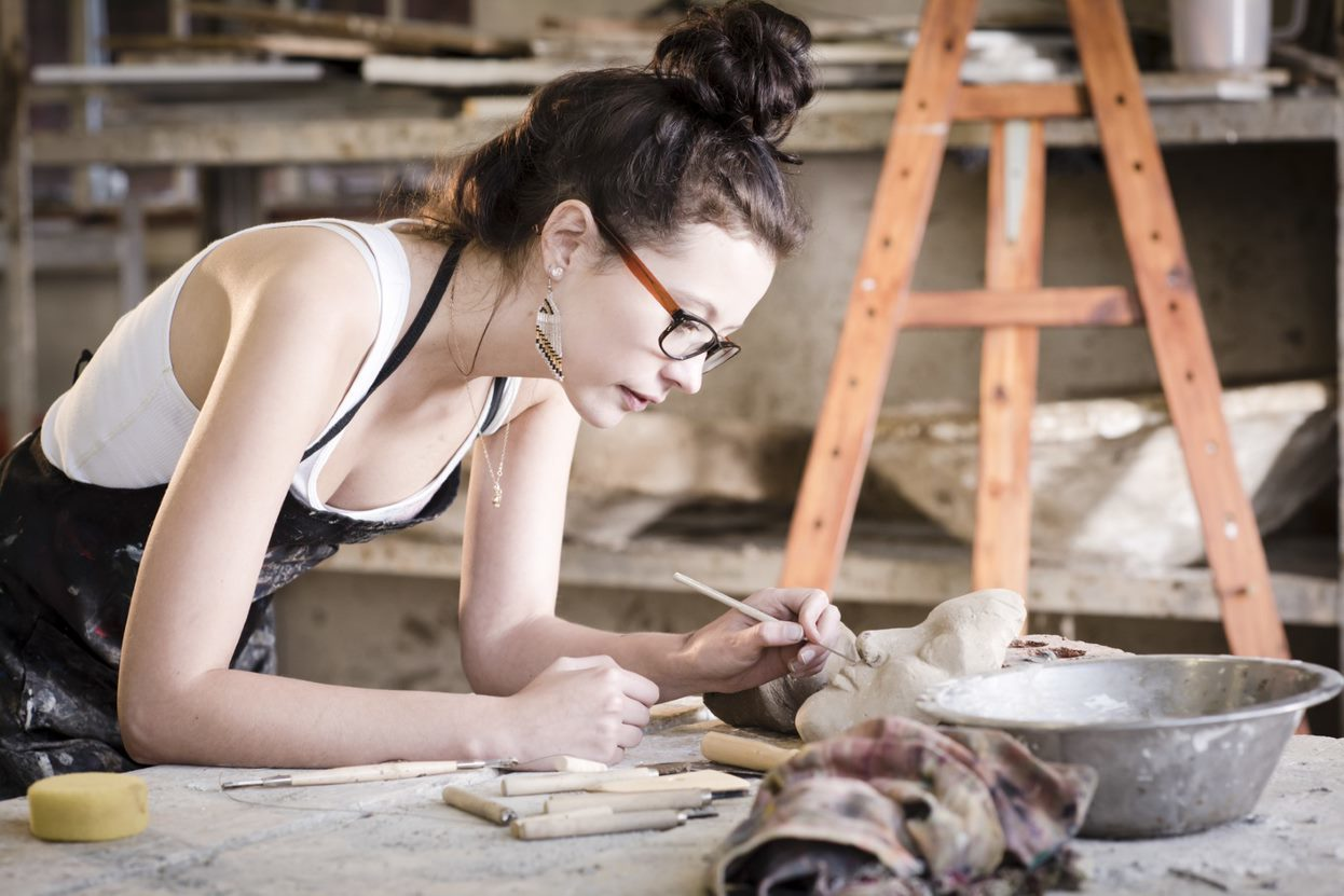 A person wearing glasses works on a ceramics project in a studio