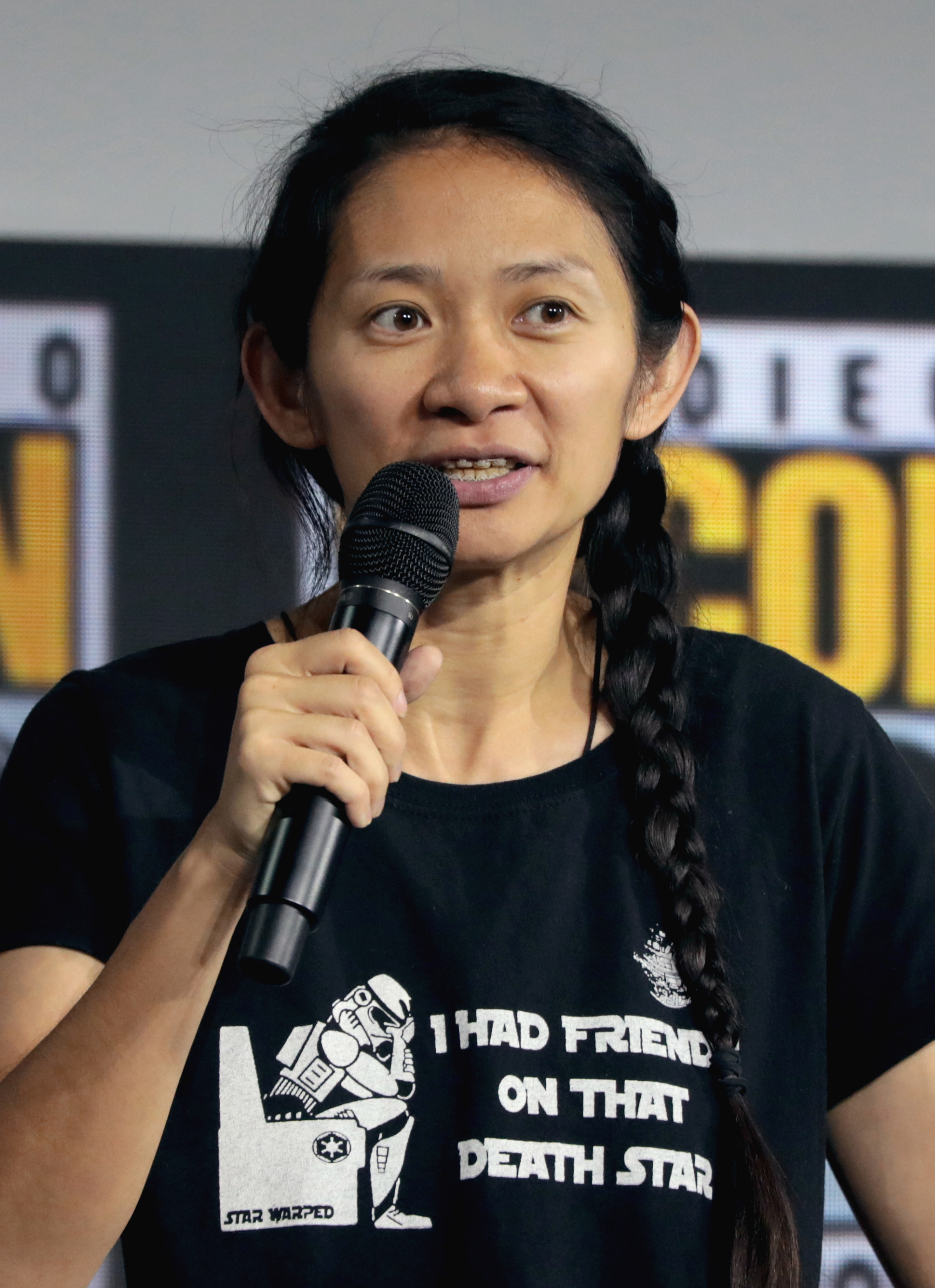 A woman with dark, braided hair wearing a t-shirt speaks into a microphone at an event