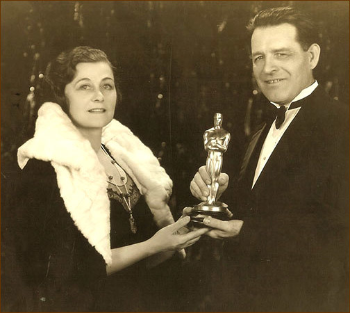 A woman receives an Academy Award statuette from a man