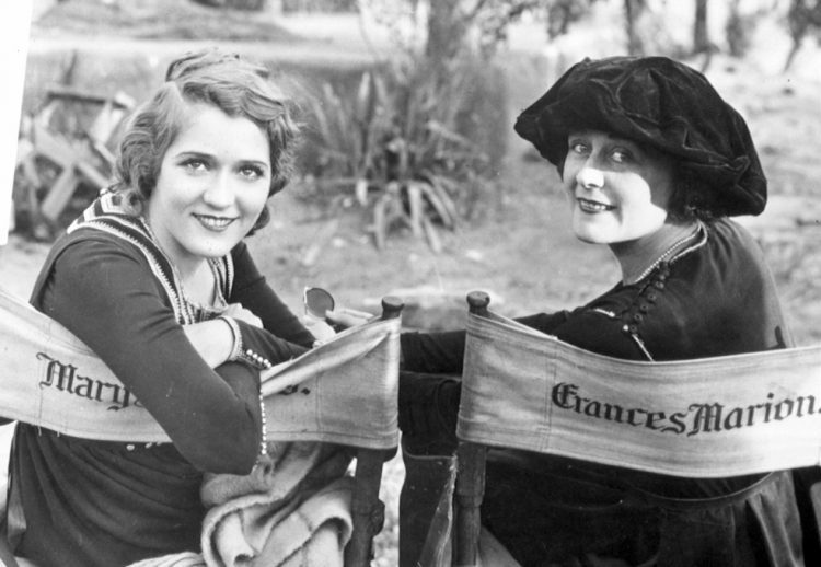 An archive photo depicts two women in director's chairs, looking back and smiling at the camera