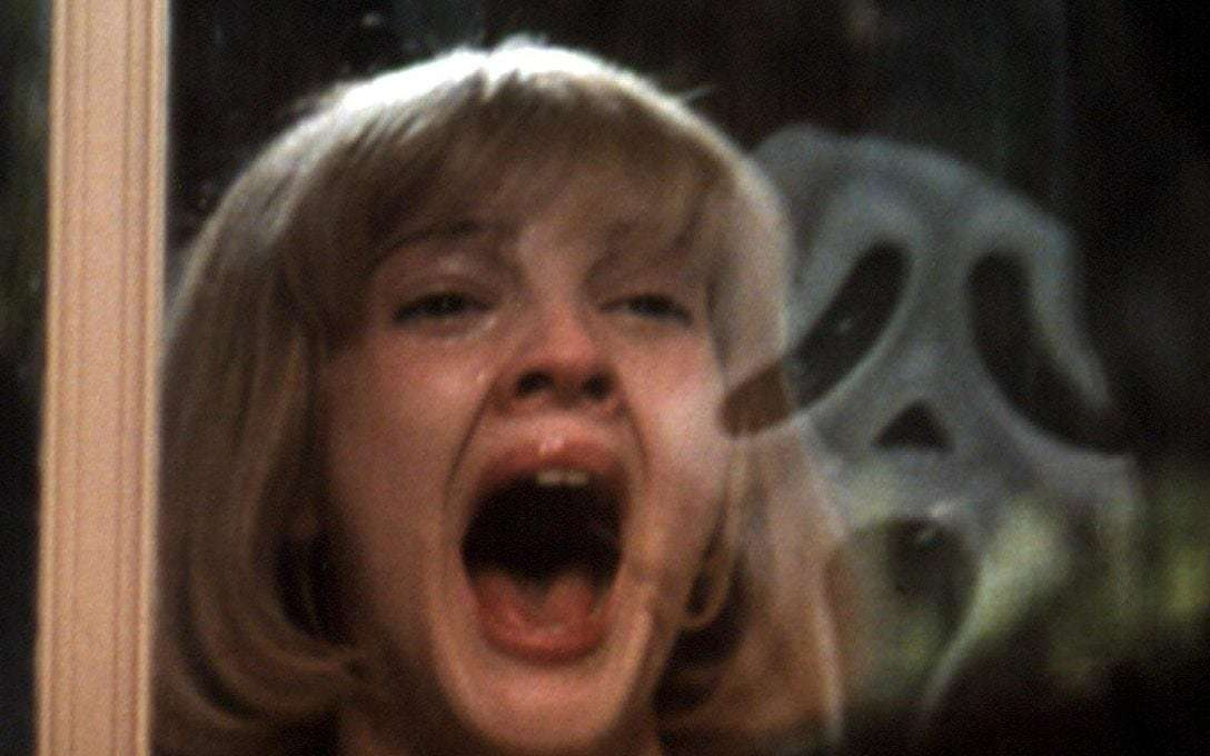 A still image from a horror film depicts a woman's screaming face alongside a reflection of a masked figure