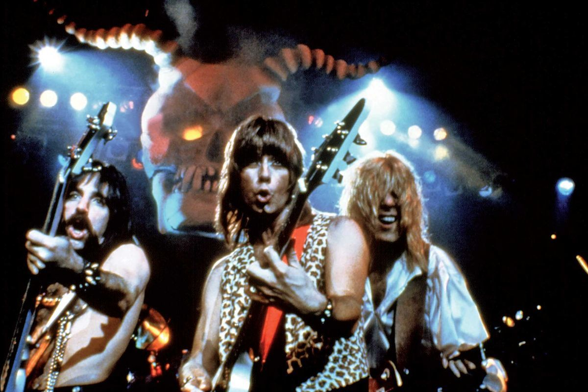 A trio of '80s rock musicians with long hair perform in front of a giant devil skull with glowing eyes