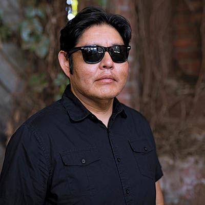 A person with short black hair and sunglasses poses for the camera