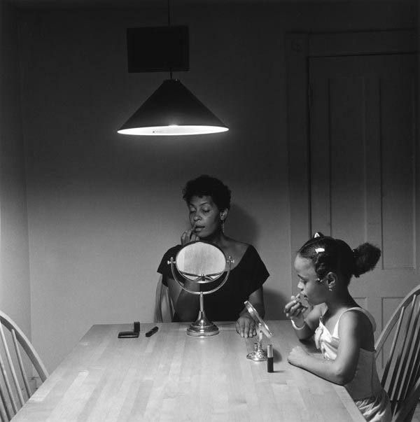A black-and-white photograph depicts a black woman and young girl applying lipstick beneath a single overhead light