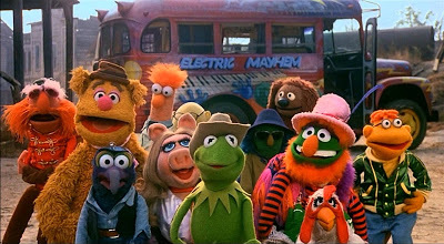 "A cast of colorful people and animal puppets pose in front of a bus emblazoned with the words ""Electric Mayhem"""