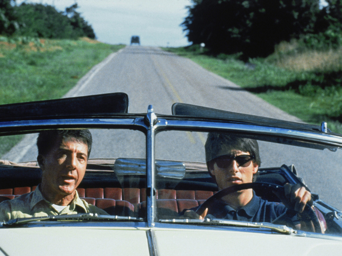 Two adults ride in a convertible on a rural highway