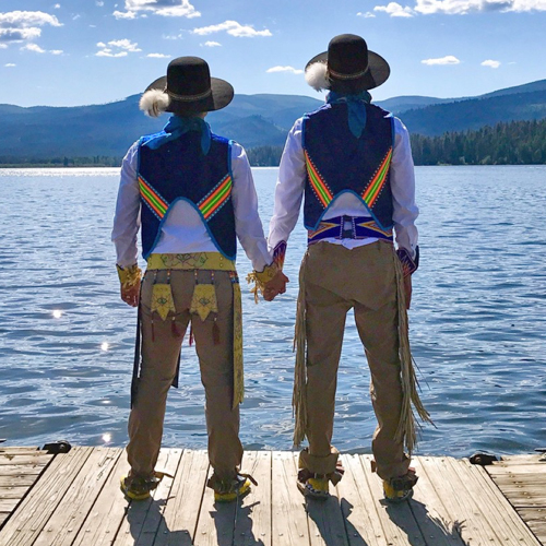 Two people in American Indian tribal regalia hold hands as they look out on the water and mountains