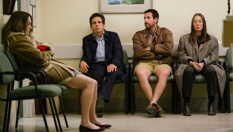 Four adults are seated in a waiting room