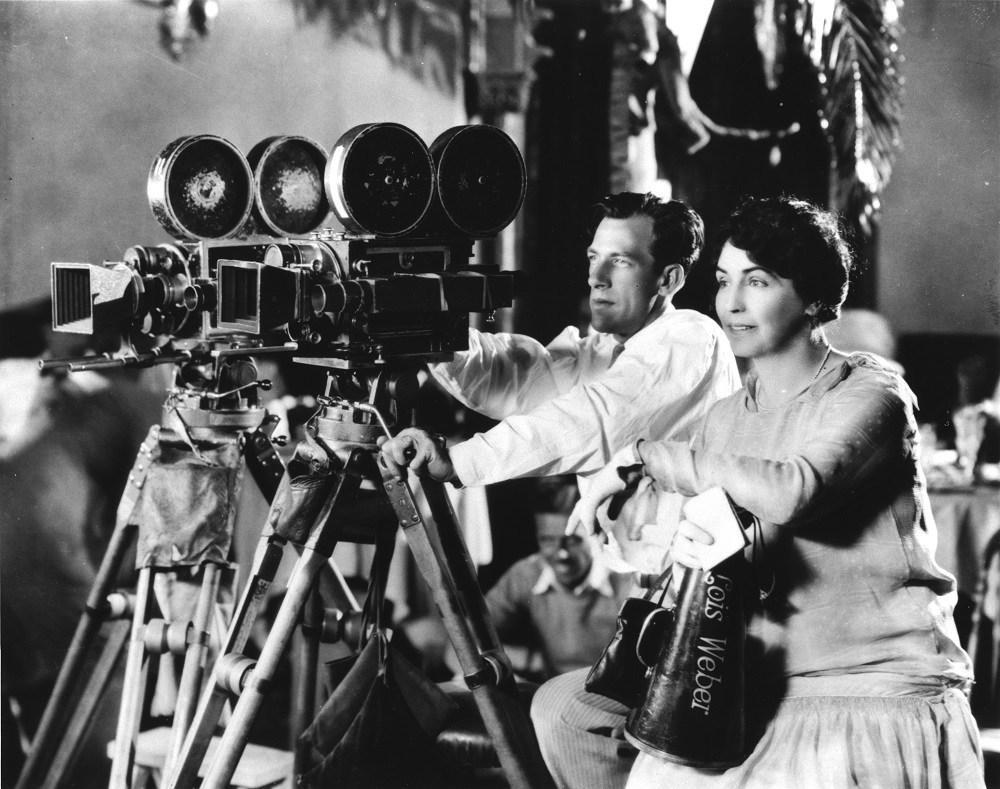 A historical photo of a woman and a man sitting behind movie cameras