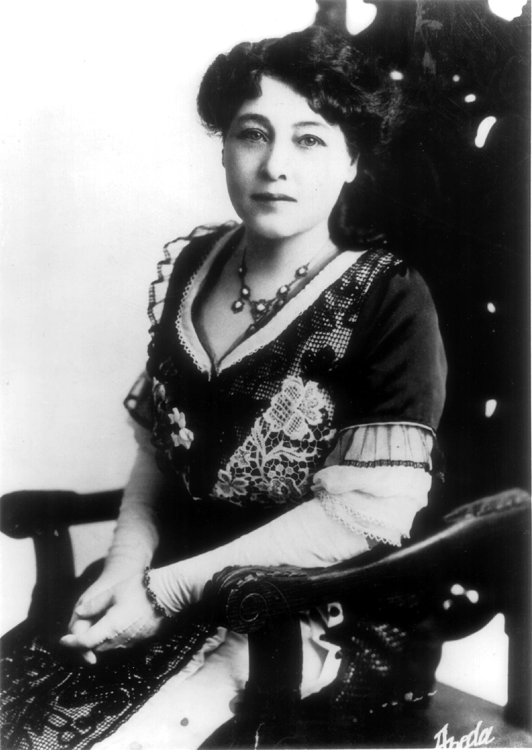 A black and white image of a woman sitting in a chair